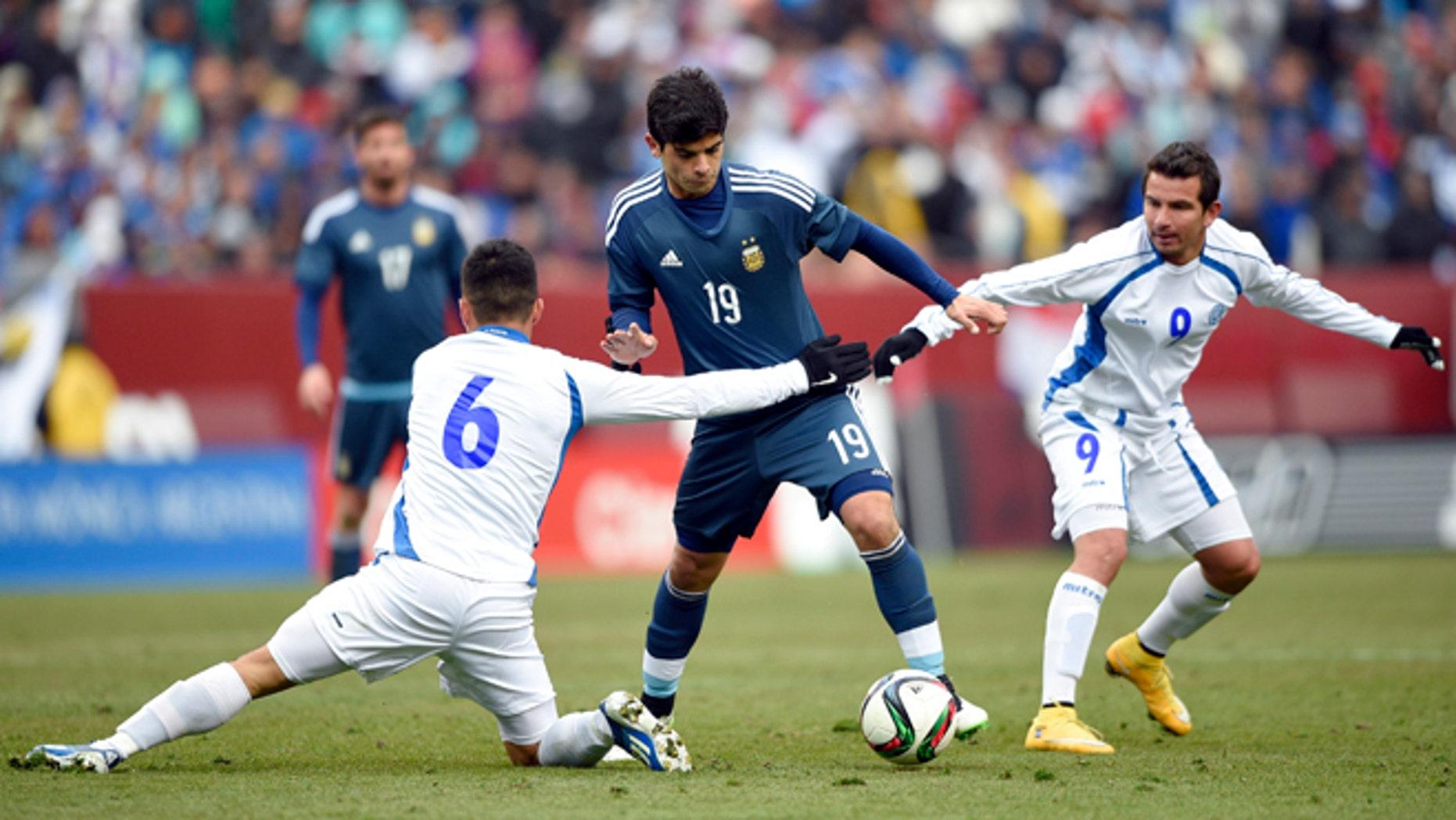 Argentina's Ever Banega battles for the ball against El Salvador's Richard Menjivar and Rafael Burgos, March 28, 2015.