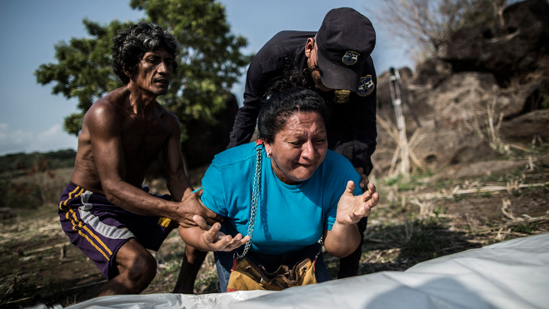 FILE - In this May 28, 2015, file photo, the sister of Alberto Hernández Escalante mourns over the body of her brother, found in a clandestine grave, in a rural area near Caserio el Chumpe, El Salvador. (AP Photo/Manu Brabo, File)