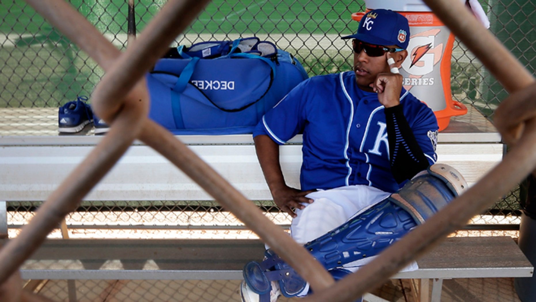 Kansas City Royals catcher Salvador Perez waits in a dugout before a drill during spring training baseball practice Tuesday, Feb. 23, 2016, in Surprise, Ariz. (AP Photo/Charlie Riedel)