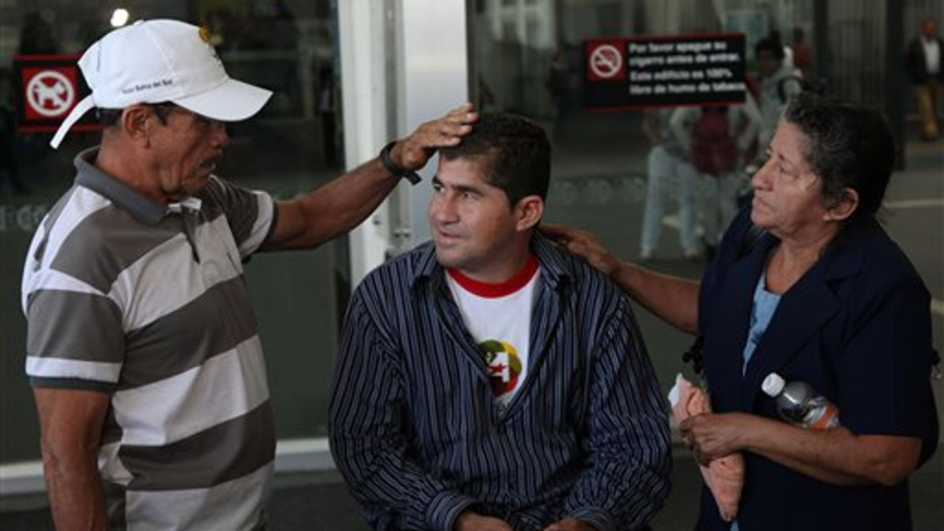 Sea survivor Jose Salvador Alvarenga, center, is flanked by his father Jose Ricardo and mother Maria Julia, before entering the waiting hall for national departures, after arriving at the airport in Mexico City, Friday, March 14, 2014. The Salvadoran fisherman, who was lost at sea for 13 months, traveled from El Salvador to Mexico to fulfill a promise he made to his dead sea mate, Mexican Ezequiel Cordoba. Alvarenga said Cordoba died a month into their ordeal because he couldn't stomach the diet of raw fish, turtles and birds. (AP Photo/Marco Ugarte)