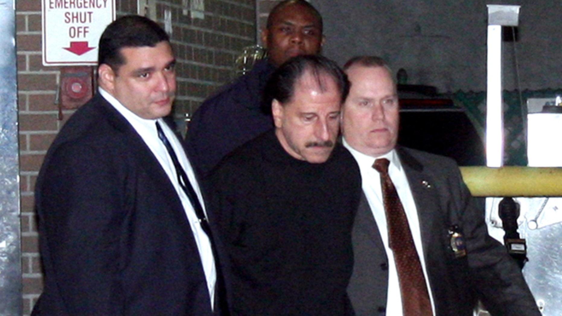 Nov. 21: Police escort Salvatore Perrone, center, from the 67th Precinct.