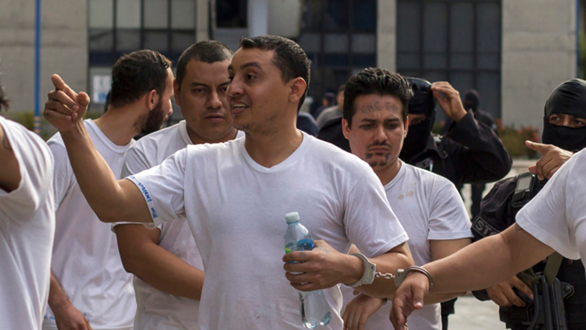 In this Tuesday, Aug. 2, 2016 photo, handcuffed to another prisoner, Marvin Quintanilla Ramos, center, an evangelical pastor accused by El Salvador Police to be the financier of Mara Salvatrucha gang, is walked out after a court hearing in San Salvador, El Salvador. Prosecutors allege that Ramos used his pastoral credentials to access prisons so he could conspire with jailed leaders of the gang. Religion, they say, was a facade to mask his real work: helping run Mara Salvatruchas street operations and directing its finances at a key moment when gangs are facing a tough crackdown by the government and are moving to diversify their criminal operations and become more corporate in makeup and structure. (AP Photo/Salvador Melendez)
