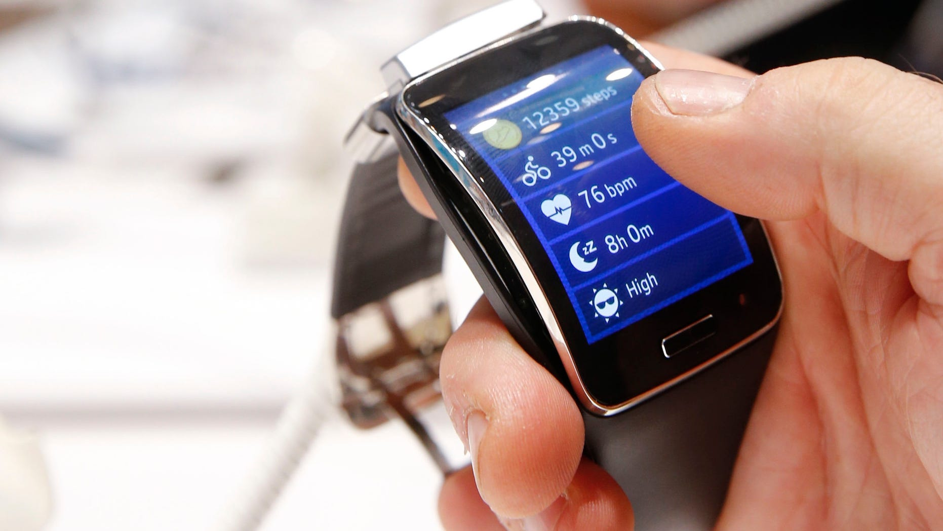 A visitor holds a Samsung Gear S smartwatch at the IFA consumer technology fair in Berlin, September 5, 2014.