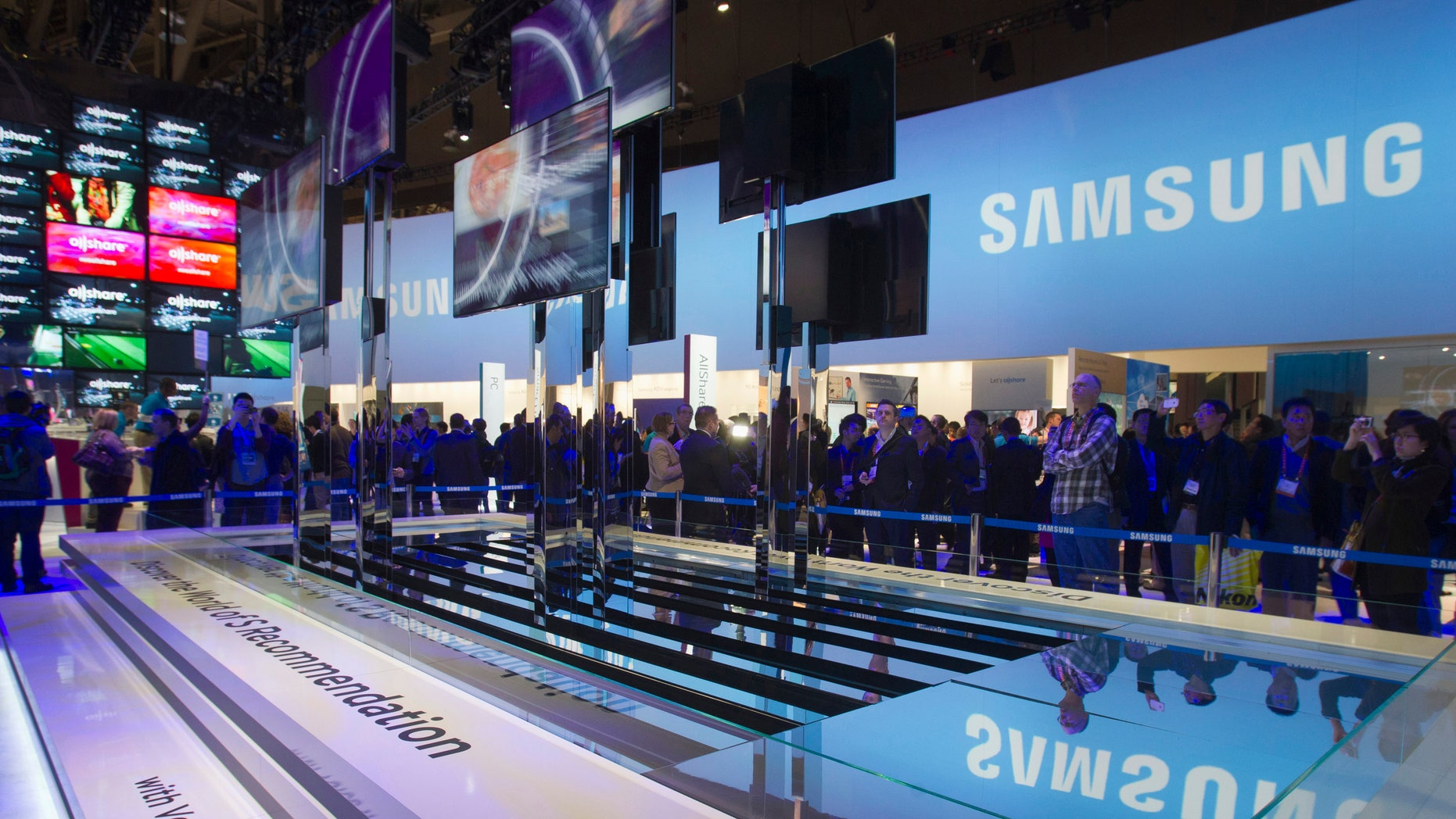 File photo - Showgoers watch a display of Samsung Smart TVs during the first day of the Consumer Electronics Show (CES) in Las Vegas Jan. 8, 2013.