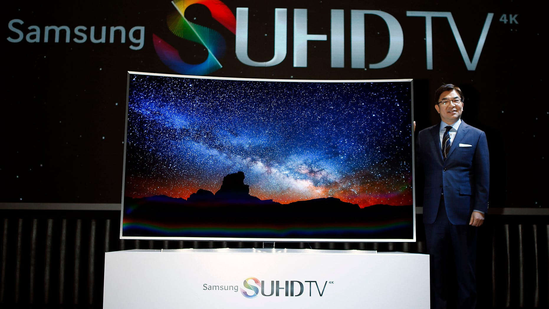 Kim Hyun-seok, head of Samsung Electronics television division, poses for photographs with a Samsung Electronics smart TV during its launch event in Seoul February 5, 2015.