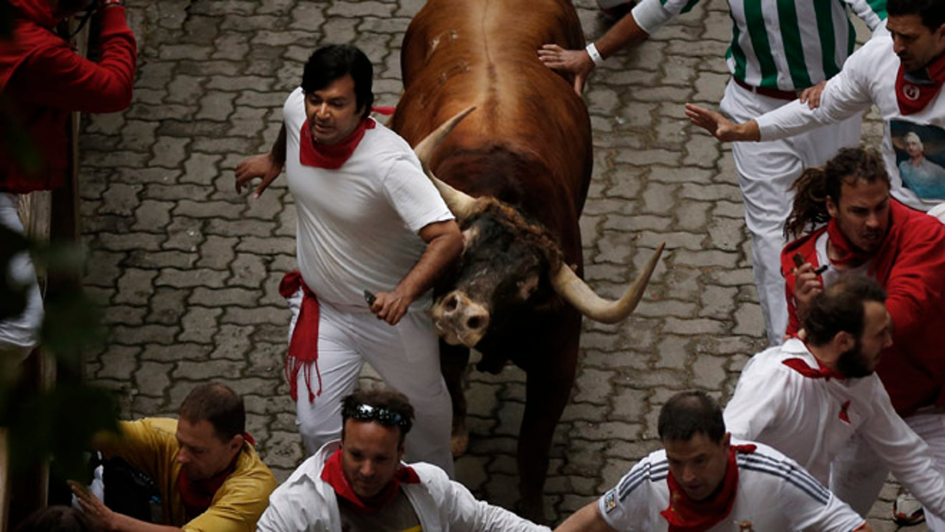 July 9, 2014: A Victoriano del Rio ranch fighting bull tosses a reveler during the running of the bulls of the San Fermin festival, in Pamplona, Spain.