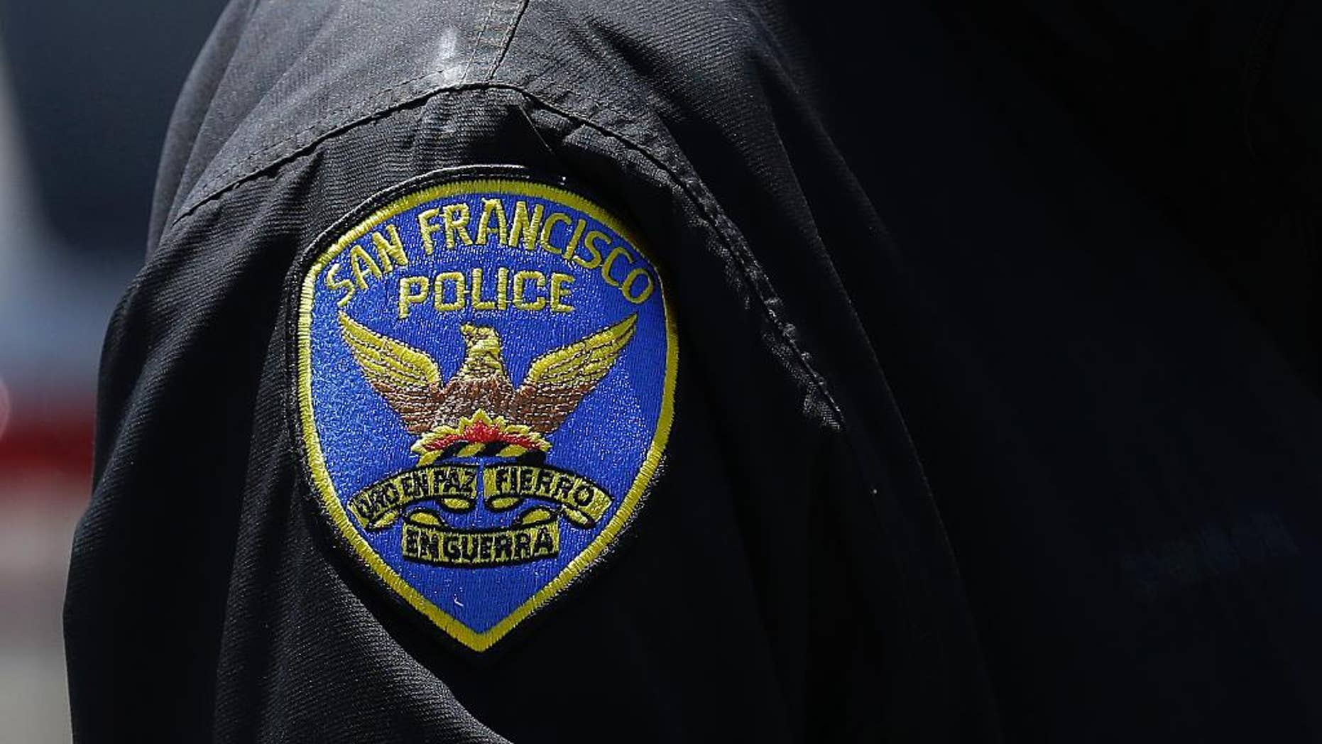 In this May 12, 2015 photo, a San Francisco Police officer stands on a street in San Francisco. The original charges were shocking enough: six San Francisco police officers were accused of stealing from suspects living in seedy residential hotels. Then federal prosecutors released racist, homophobic and ethnically insensitive email and text messages exchanged among more than a dozen officers, prompting the San Francisco district attorney to launch a wide-ranging investigation of the police department while considering dismissing up to 3,000 criminal cases involving the officers. (AP Photo/Jeff Chiu)