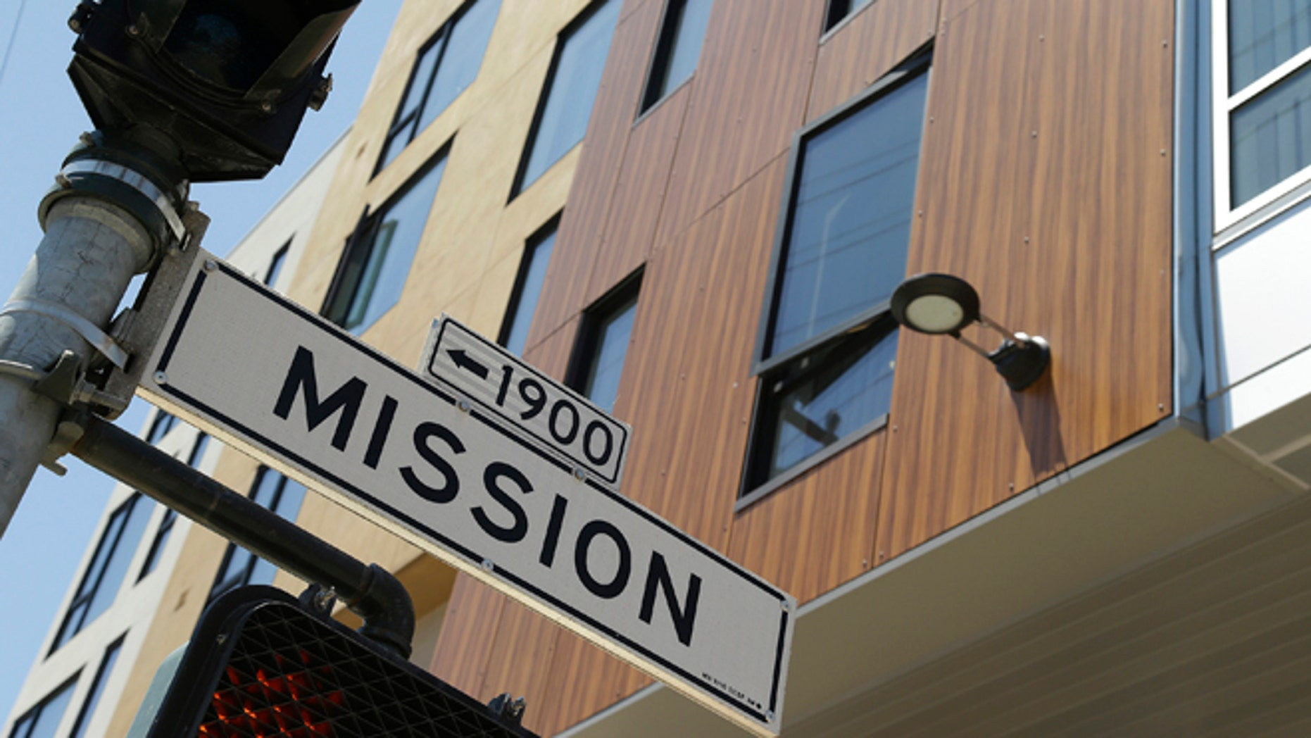 A street sign hangs outside a new apartment building on Mission Street, Tuesday, June 2, 2015, in San Francisco. Finding a place to live has become so expensive and emotional that city supervisors are considering a 45-day moratorium on luxury housing in the Mission District, which has long been one of the most diverse neighborhoods in the city. (AP Photo/Eric Risberg)