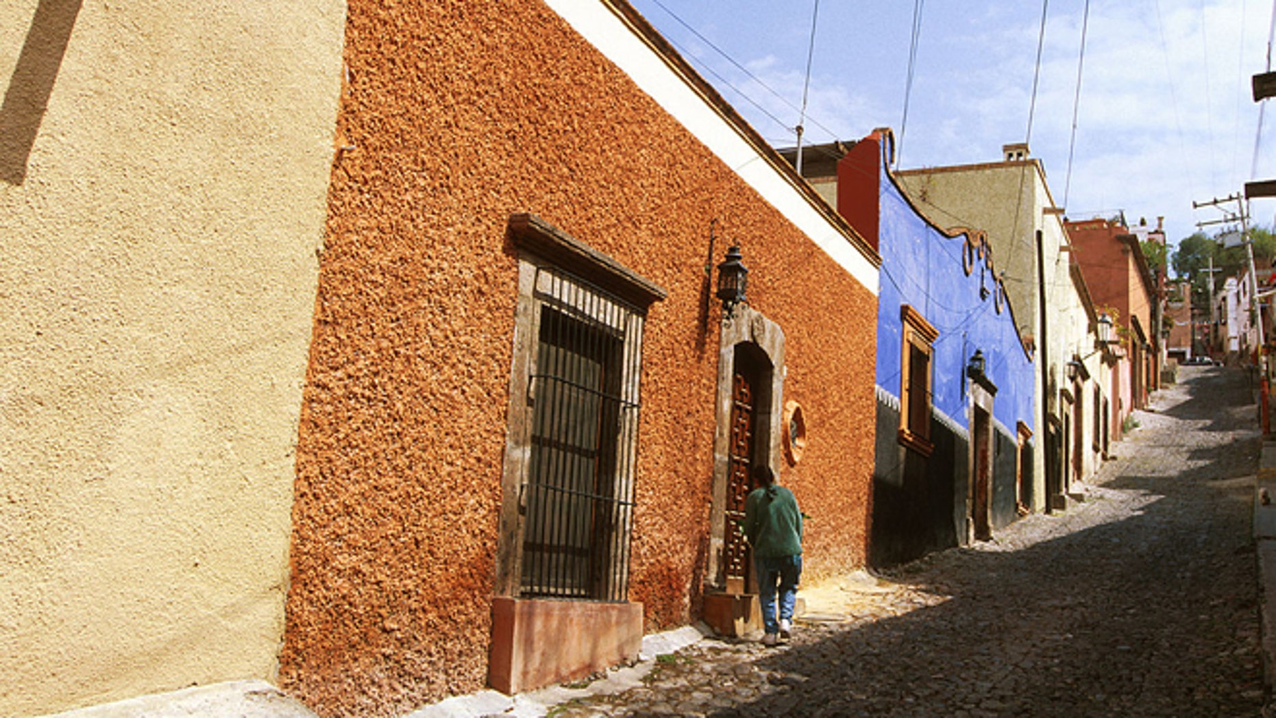 Mexico, San Miguel De Allende, Person Standing In Front Of A Doorway On A Cobblestone Roadway. (Photo by Education Images/UIG via Getty Images)