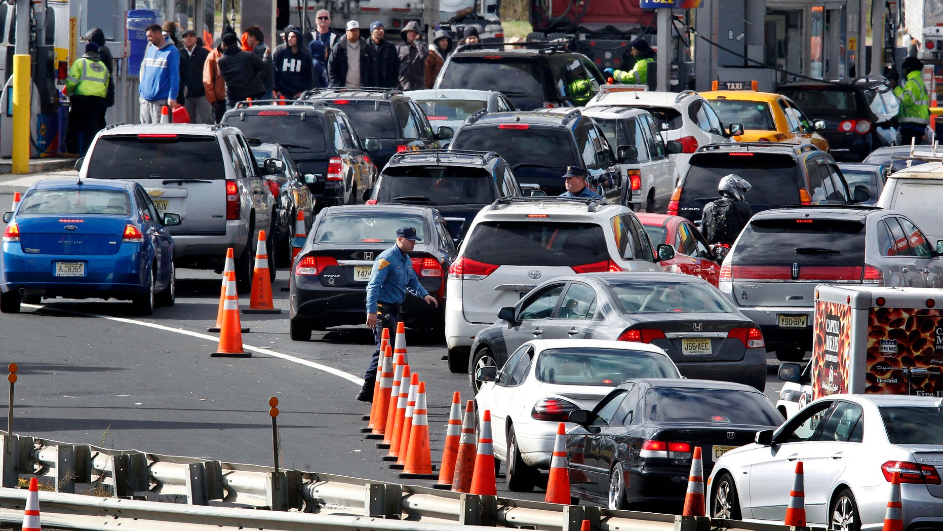 New Jersey state troopers keep order as motorists line up to purchase gasoline at the Thomas A. Edison service area on the New Jersey Turnpike, Saturday, Nov. 3, 2012, near Woodbridge, N.J. (AP Photo/Mel Evans)