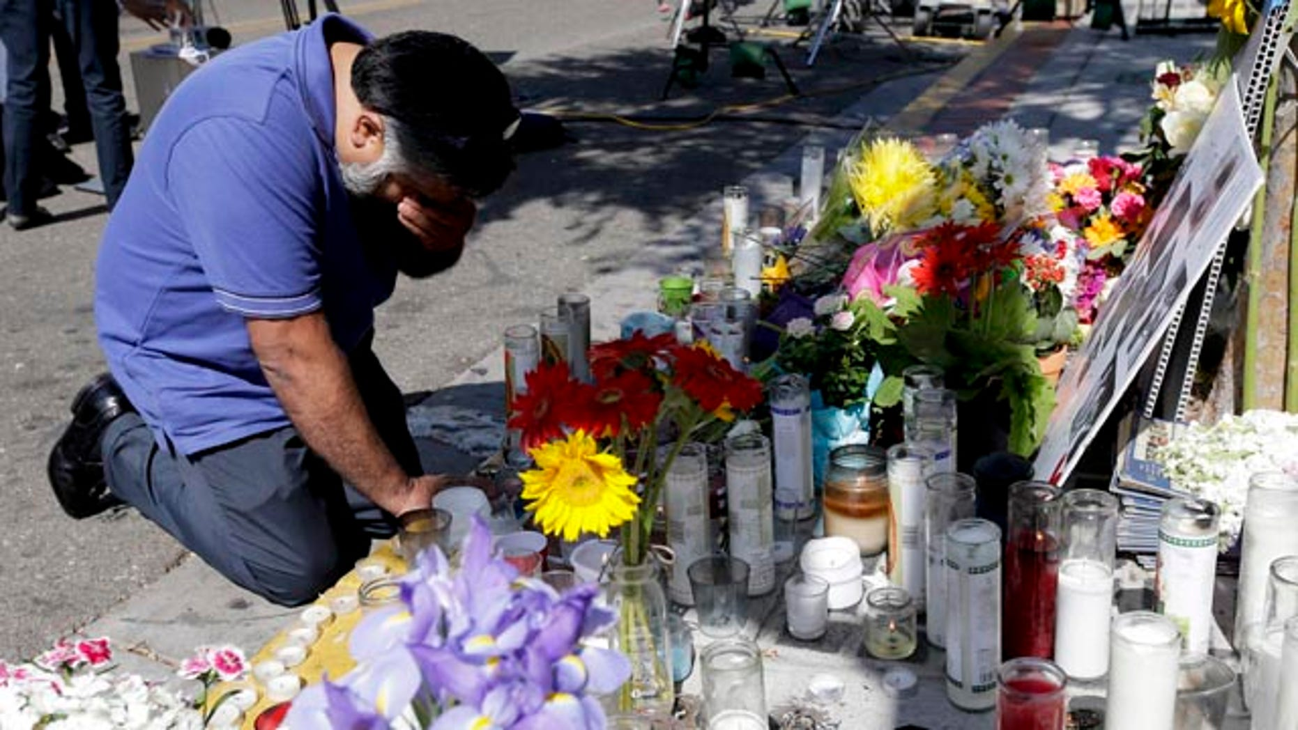 May 25, 2014: Jose Cardoso pays his respects at a makeshift memorial in front of the IV Deli Mart, where part of Friday night's mass shooting took place.