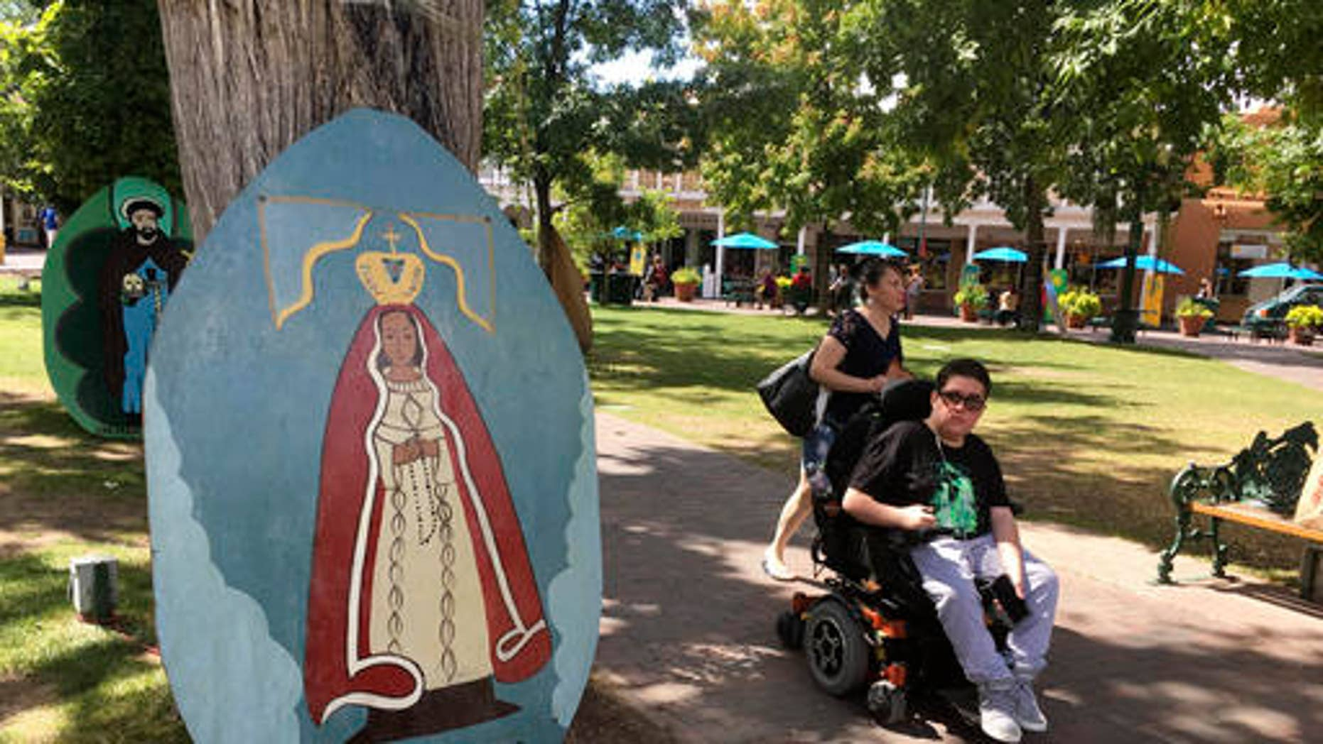 This Sept. 1, 2016 photo shows visitors of Santa Fe Plaza pass by an image of La Conquistadora, oldest statue of the Blessed Virgin Mary in the United States, as organizers prepare for the annual Santa Fe Fiesta.  For centuries, northern New Mexico Hispanic residents have held an elaborate festival in Santa Fe in honor of Spanish conquistador Don Diego De Vargasâ who reclaimed the city following an American Indian revolt.  But after 301 years, an emboldened group of Native American activists say itâs time to change a celebration centered around the conquest of New Mexicoâs Pueblo tribes.  (AP Photo/Russell Contreras)