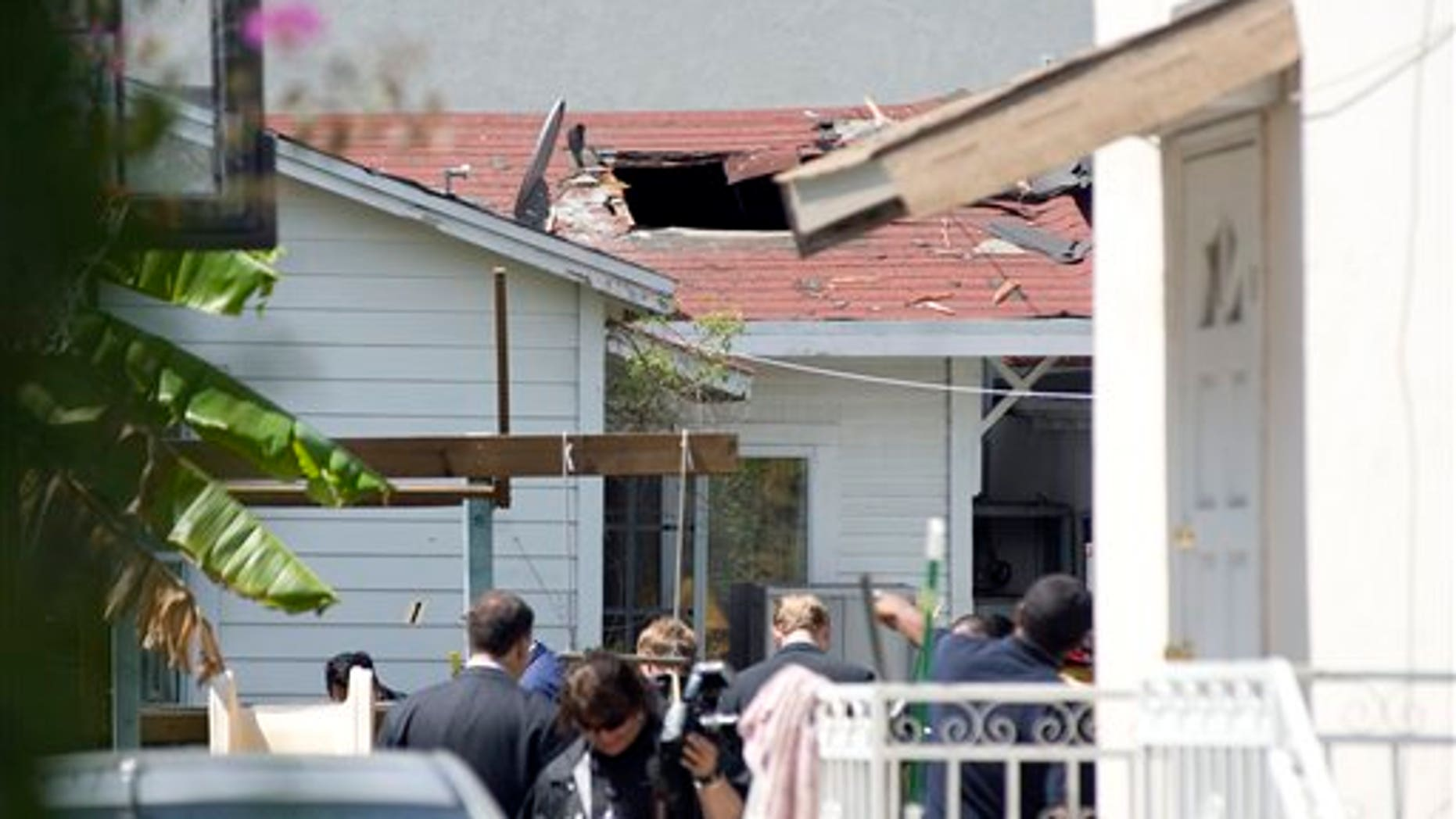 April 7: A large hole is left after police and firefighters removed a device from the roof of a home in Santa Monica, California.