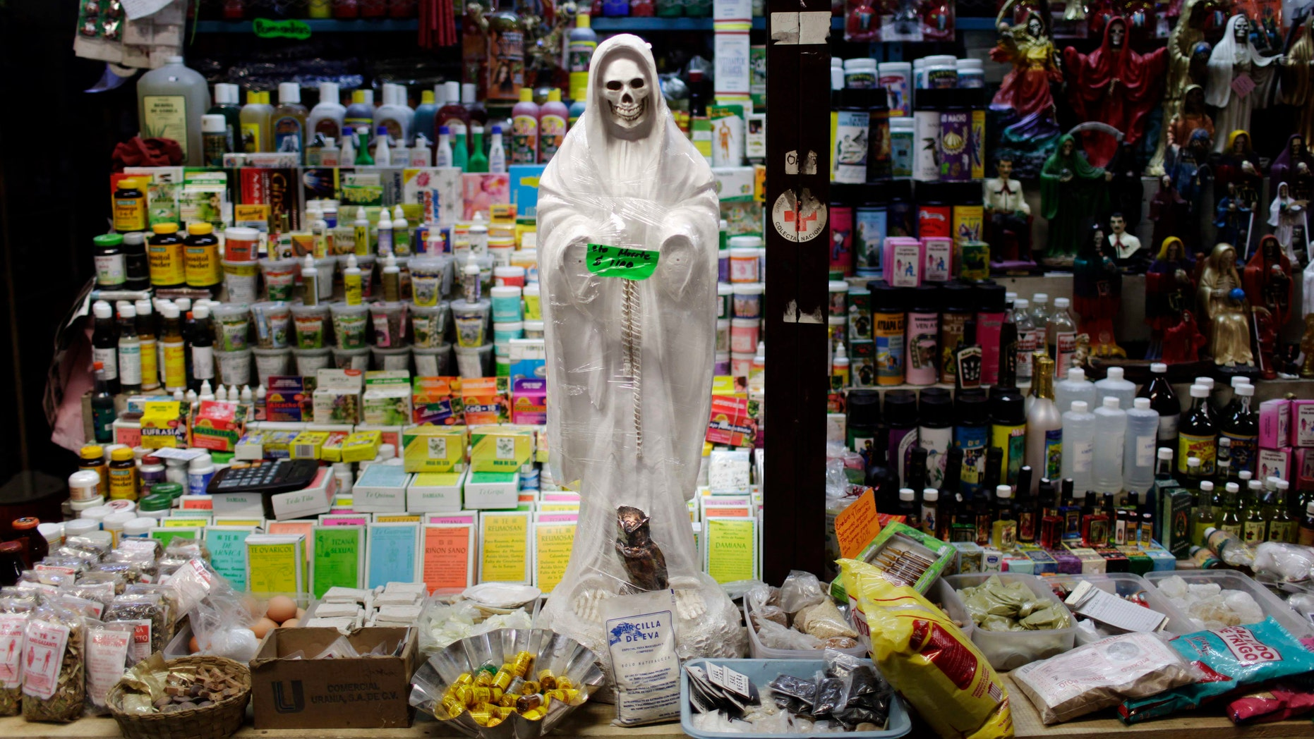 "In this April 9, 2009 file photo, a skeletal figure representing the folk saint known in Mexico as ""Santa Muerte"" or ""Death Saint,"" sits in a vendor's stall at a market in Ciudad Juárez, Mexico. (AP Photo/Rodrigo Abd, File)"