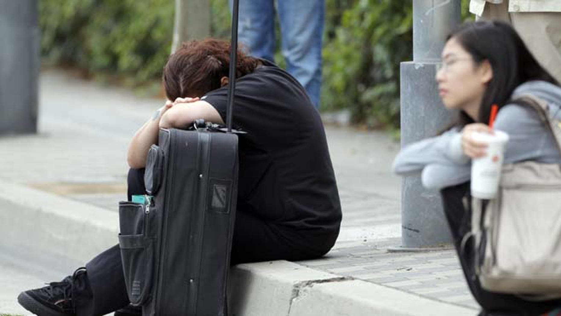June 7, 2013: A Santa Monica College student waits for police clearance to pick up her vehicle after a shooting on campus in Santa Monica, Calif.