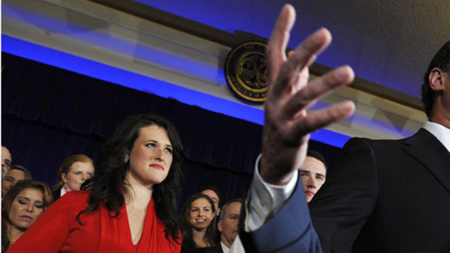 Former Pennsylvania Sen. Rick Santorum, right, speaks as his daughter, Elizabeth, looks on, Saturday, Jan. 21, 2012, in Charleston, S.C. (AP Photo/Rainier Ehrhardt)