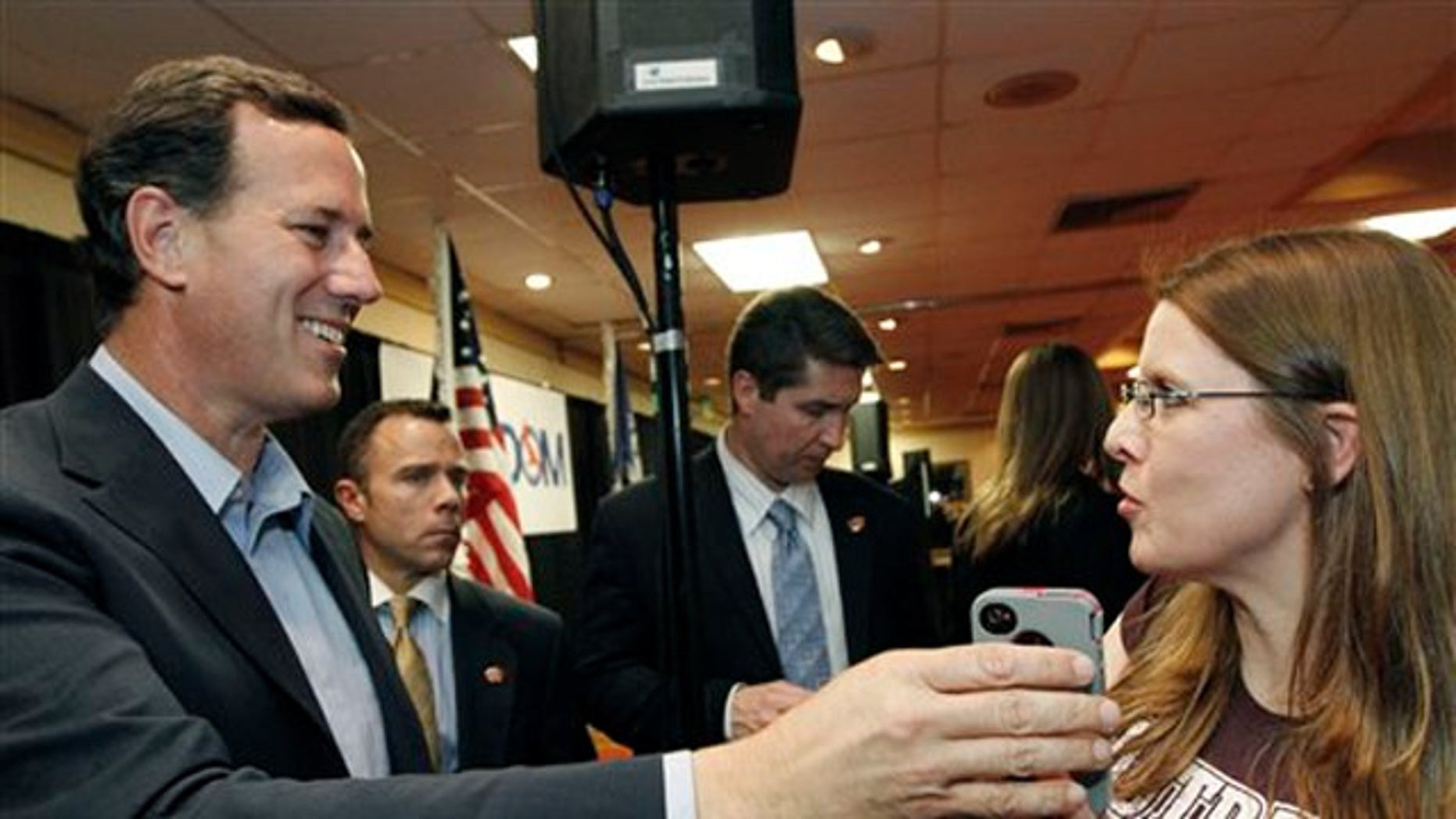 Rick Santorum, takes the phone from Allison Patterson to speak to her husband, a supporter who could not make the rally in Shreveport, La., Friday, March 23, 2012.