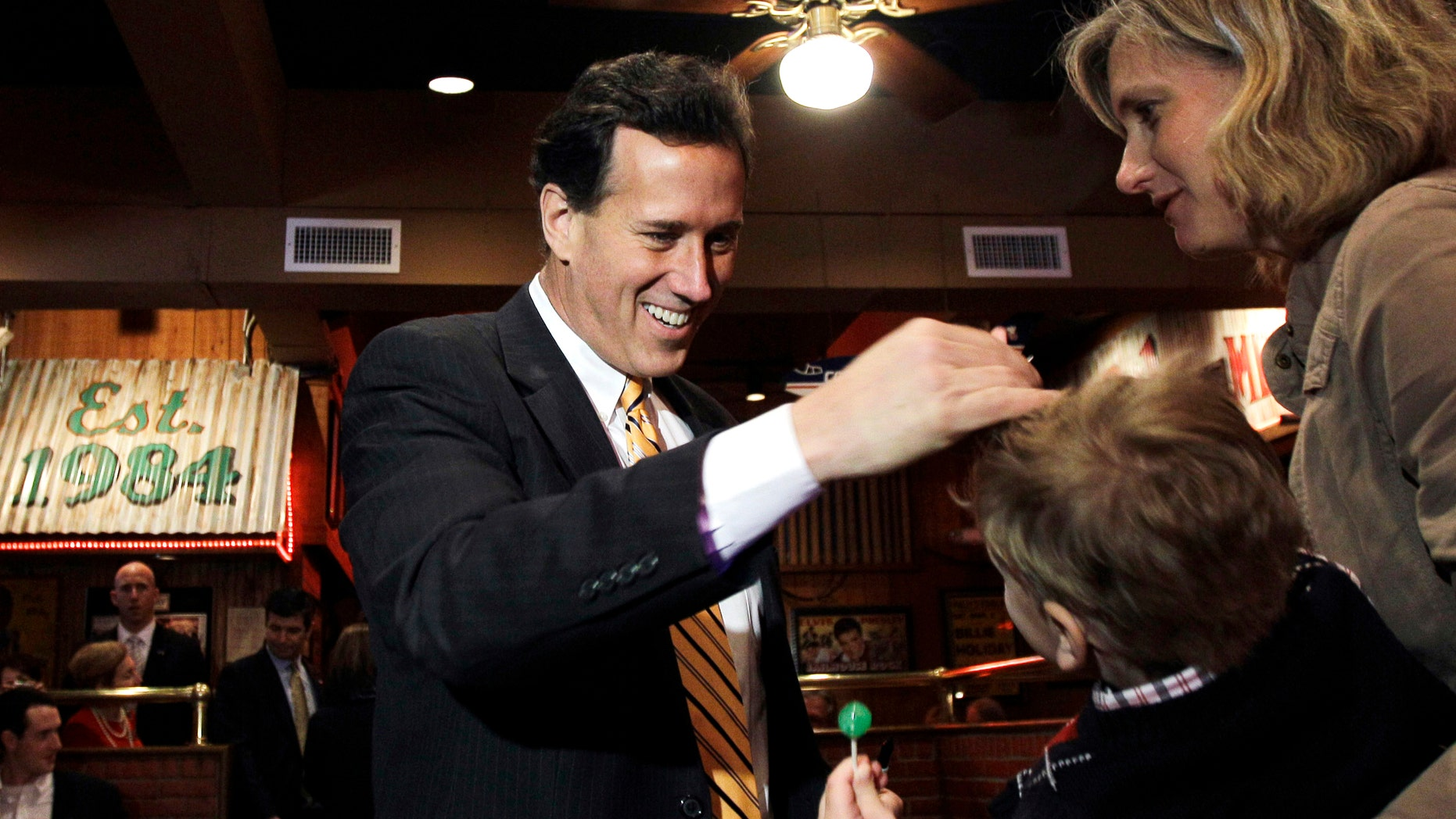 Republican presidential candidate, former Pennsylvania Sen. Rick Santorum, left, greets diners during a meet and greet at Corky's BBQ, Sunday, March 4, 2012, in Memphis, Tenn. (AP Photo/Eric Gay)