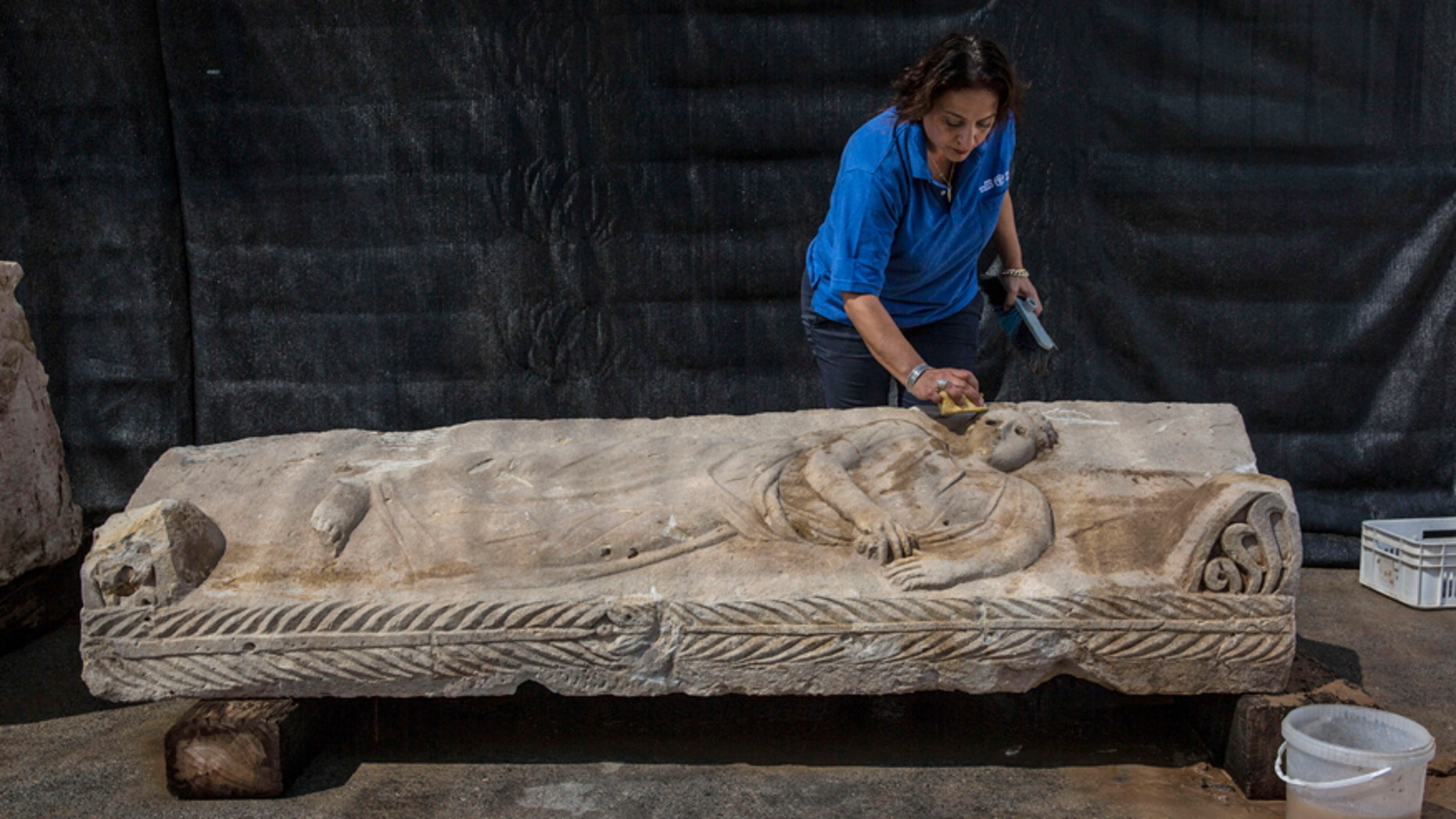 An Israeli Antiquities Authority employee cleans an 1,800 years old stone sarcophagus.