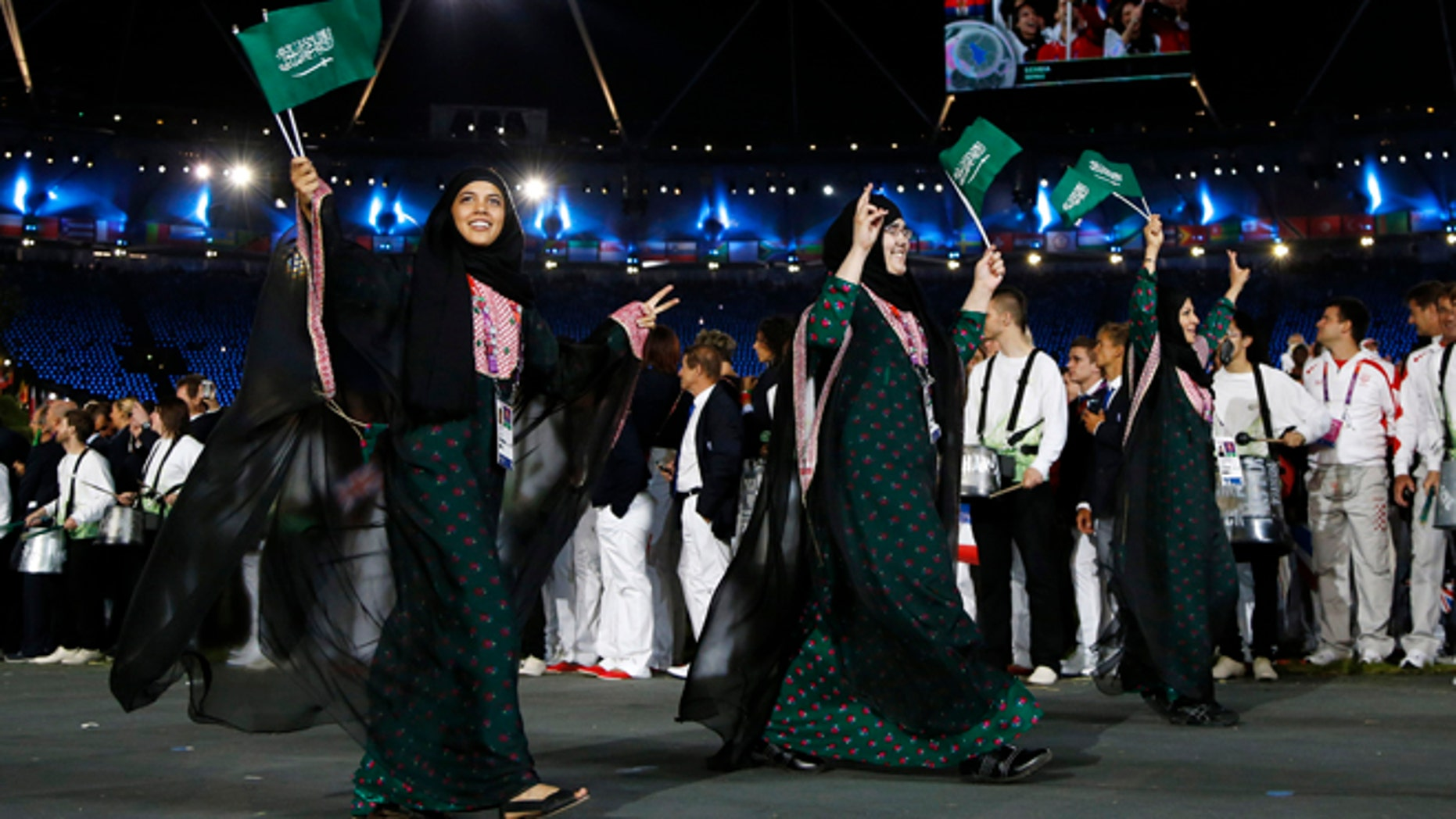 July 27, 2012: Saudi Arabia's athletes parade, Wojdan Ali Seraj Abdulrahim Shaherkani , center, during the Opening Ceremony at the 2012 Summer Olympics, in London.