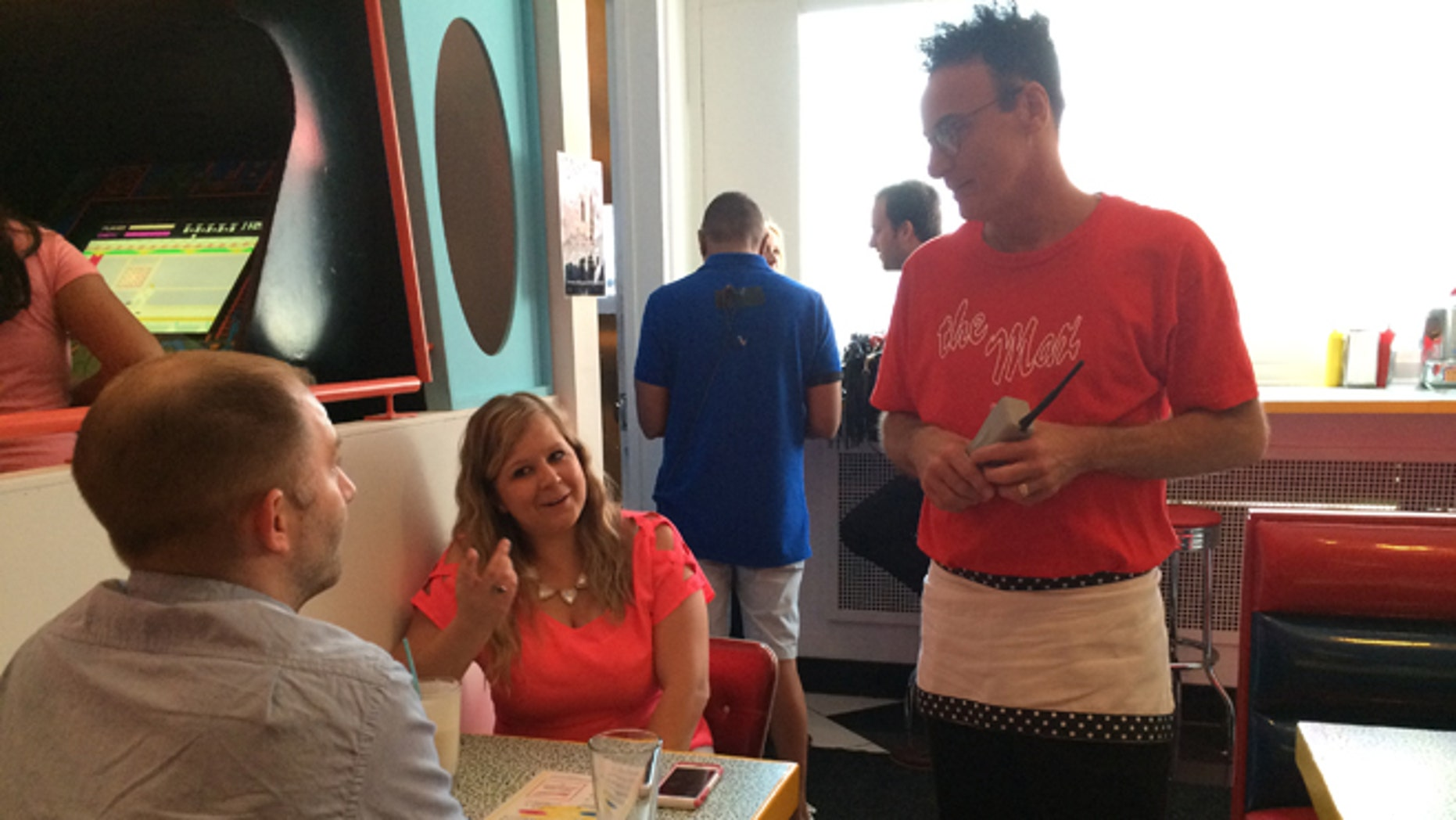 """In this Wednesday, June 1, 2016 photo, original """"Saved by the Bell"""" castmember Ed Alonzo, right, talks to Steve Gross and Tiffany Gross at pop-up restaurant Saved by the Max in Chicago. A vacant restaurant space in Chicagoâs Wicker Park neighborhood has become a replica of The Max, the fictitious hangout from the TV sitcom """"Saved by the Bell."""" (AP Photo/Terry Tang)"""