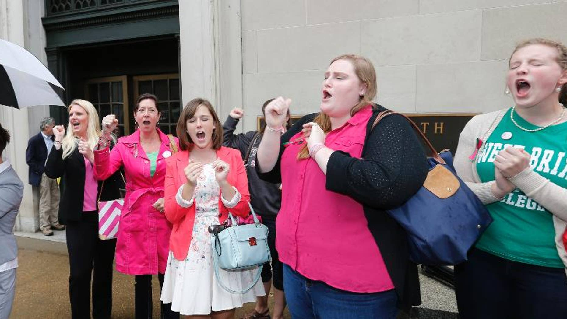 FILE - In a Thursday, June 4, 2015 file photo, Sweet Briar College alumni do a cheer for the school after a hearing on the closure of Sweet Briar college at the Supreme Court of Virginia in Richmond, Va. Sweet Briar President Phillip C. Stone marvels at the energy of passionate alumnae who helped save the school just a few months ago from closure. But he knows without a serious change in fortune, the salvation will only be temporary. (AP Photo/Steve Helber, File)