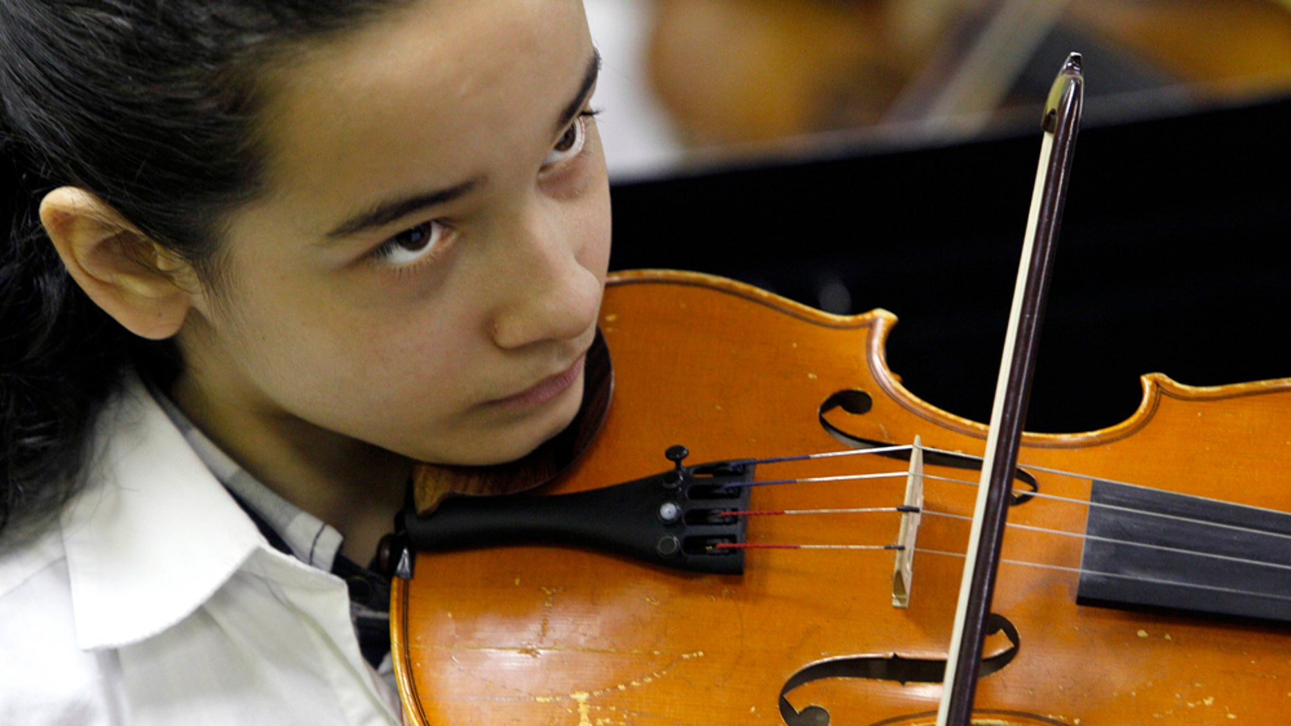 """In this May 5, 2011 photo, Nidalis Burgos keeps her eye on the conductor during a rehearsal for the after-school orchestra at Lafayette Specialty School in Chicago. Nadalis' mother calls her daughter's violin her """"soul mate."""" She practices anywhere she can, in her bedroom, in the kitchen, on her back porch so she can hear the sound reverberate off the brick apartment buildings that line the alley. Usually, she warms up with """"Ode to Joy,"""" her mother's favorite song, and a fitting theme for a girl who truly seems to love playing. (AP Photo/Charles Rex Arbogast)"""