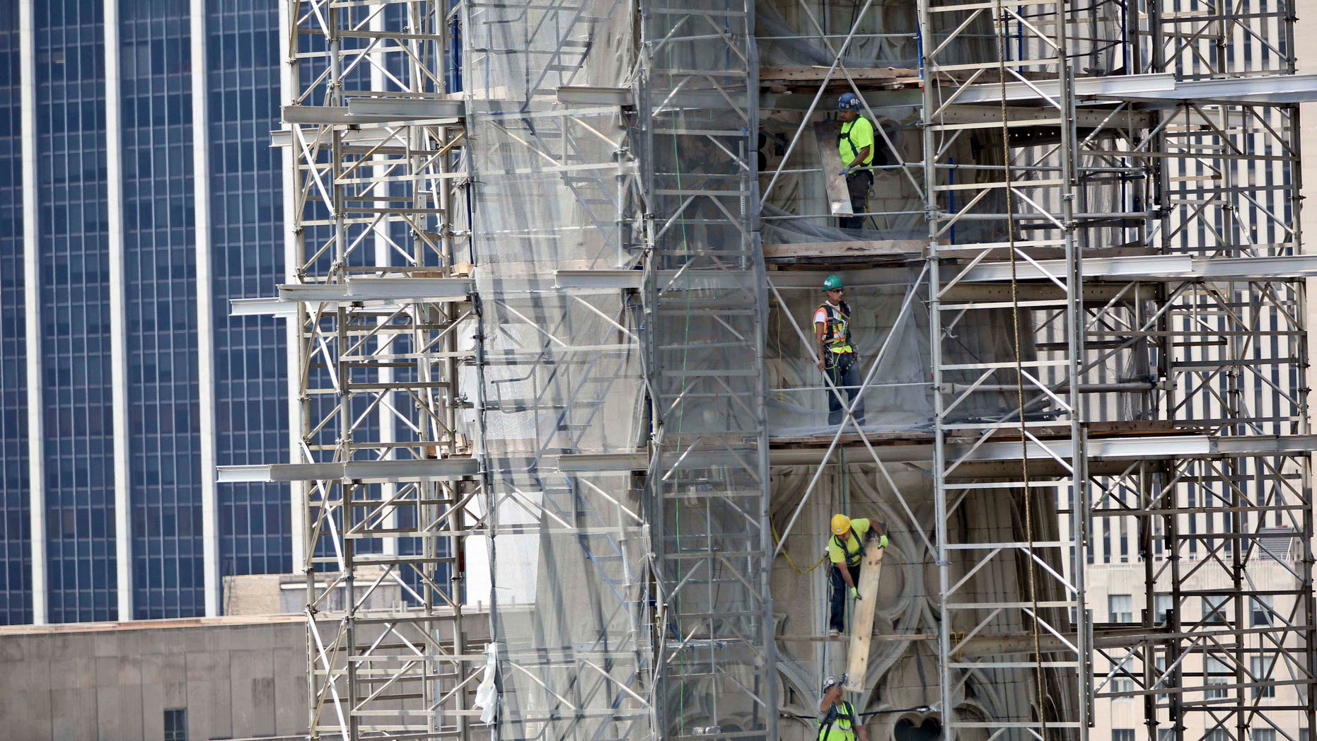 In this June 18, 2013, file photo, contractors take down the scaffolding on the North Tower of St. Patrick's Cathedral in New York.