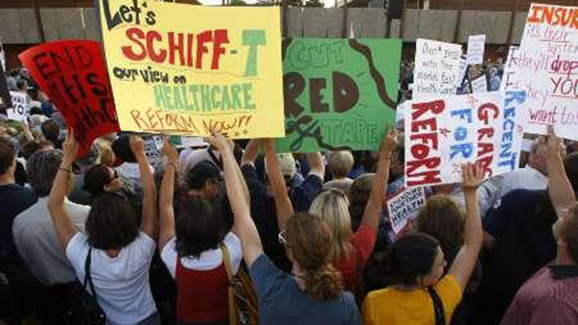 People hold up signs as they attend a town hall meeting on healthcare reform sponsored by Rep. Adam Schiff, D-Calif., in Alhambra, California, August 11, 2009. (Reuters)