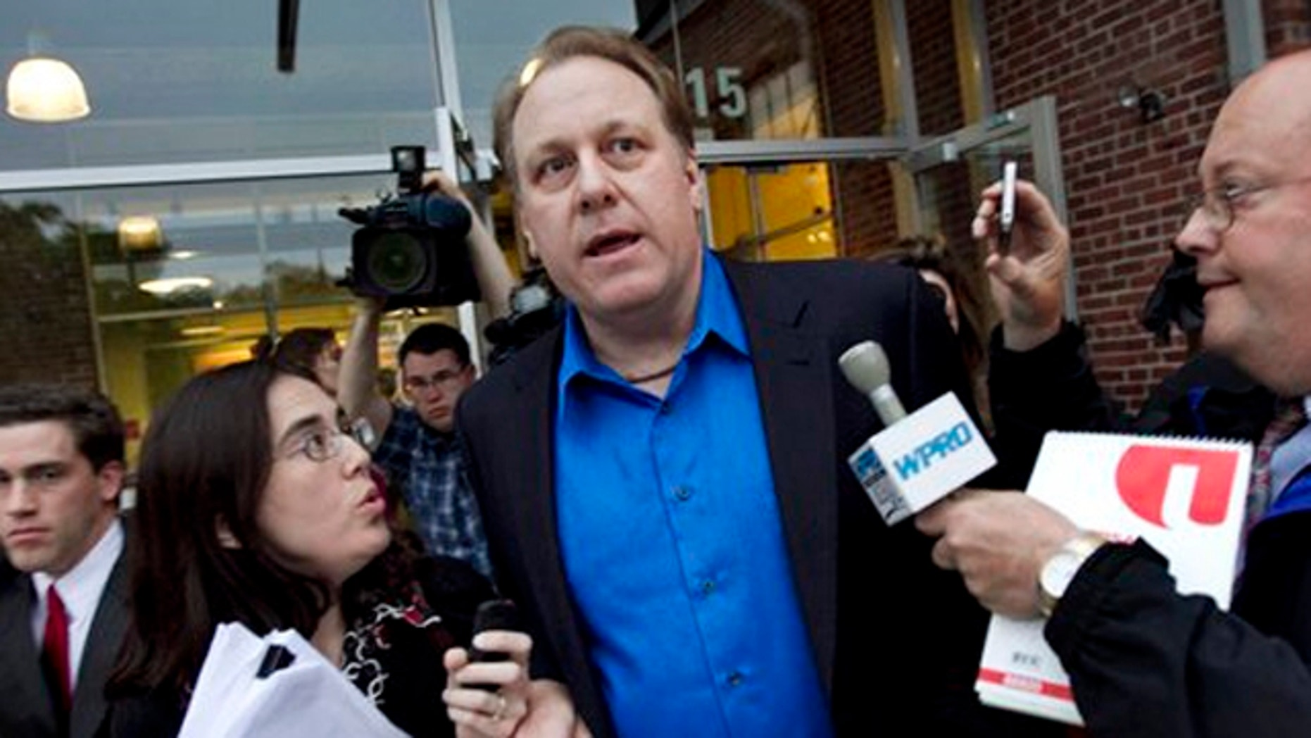 May 21, 2012: Former Boston Red Sox pitcher Curt Schilling, center, is followed by members of the media as he departs the Rhode Island Economic Development Corporation headquarters in Providence, R.I.