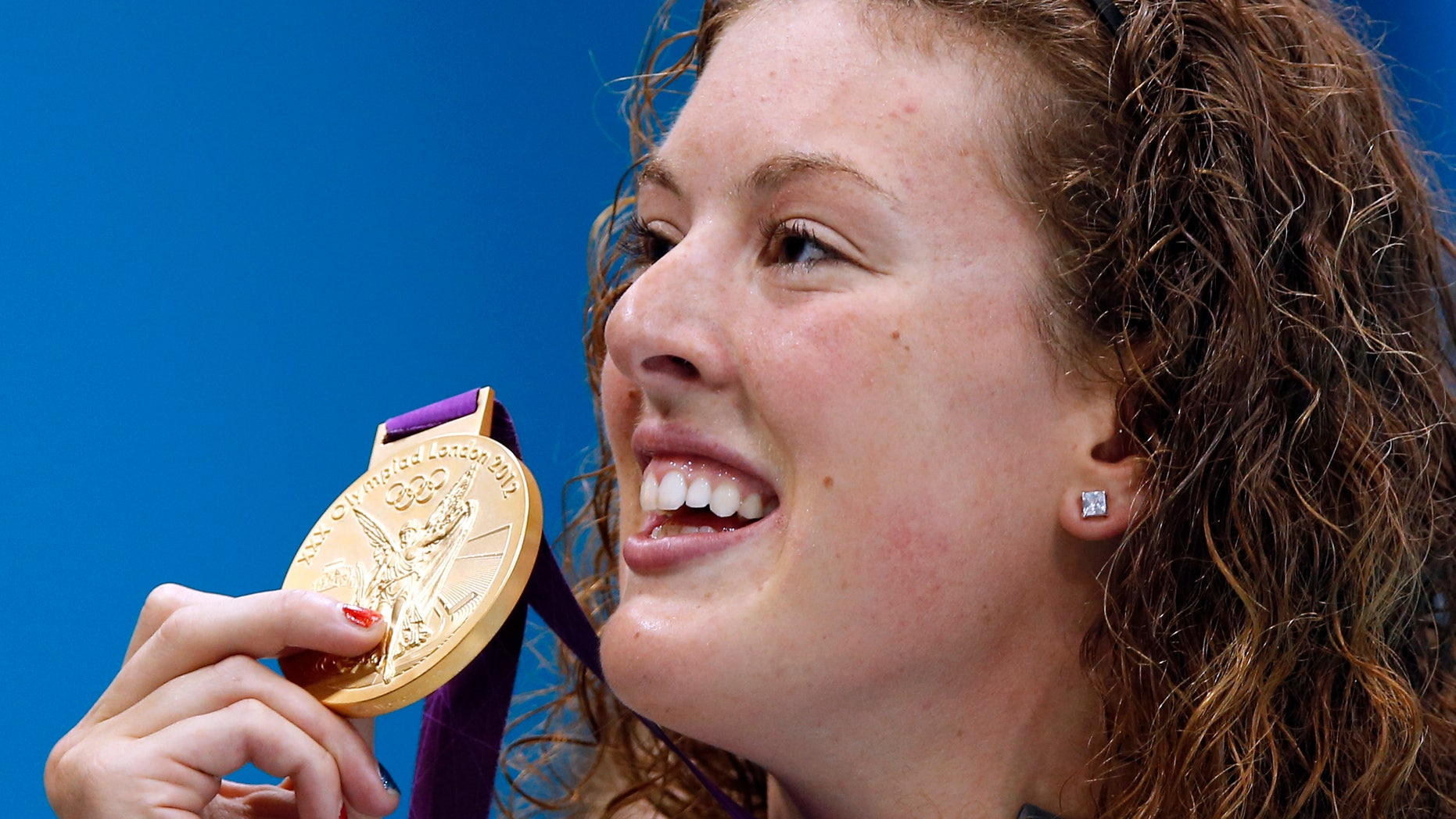 July 31, 2012: In this file photo, United States' Allison Schmitt holds her gold medal aloft after winning the women's 200-meter freestyle swimming final at the Aquatics Centre in the Olympic Park during the 2012 Summer Olympics in London.