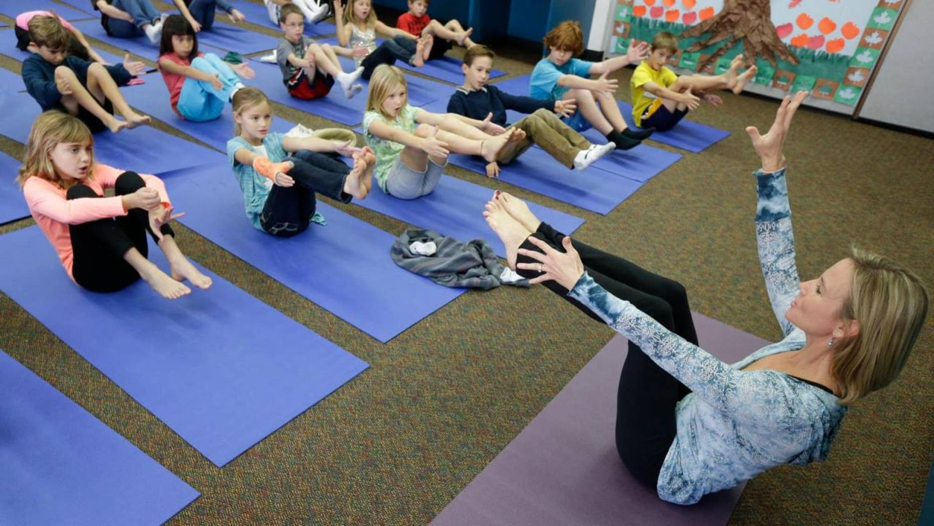 A teacher leads a group of students in a yoga class.