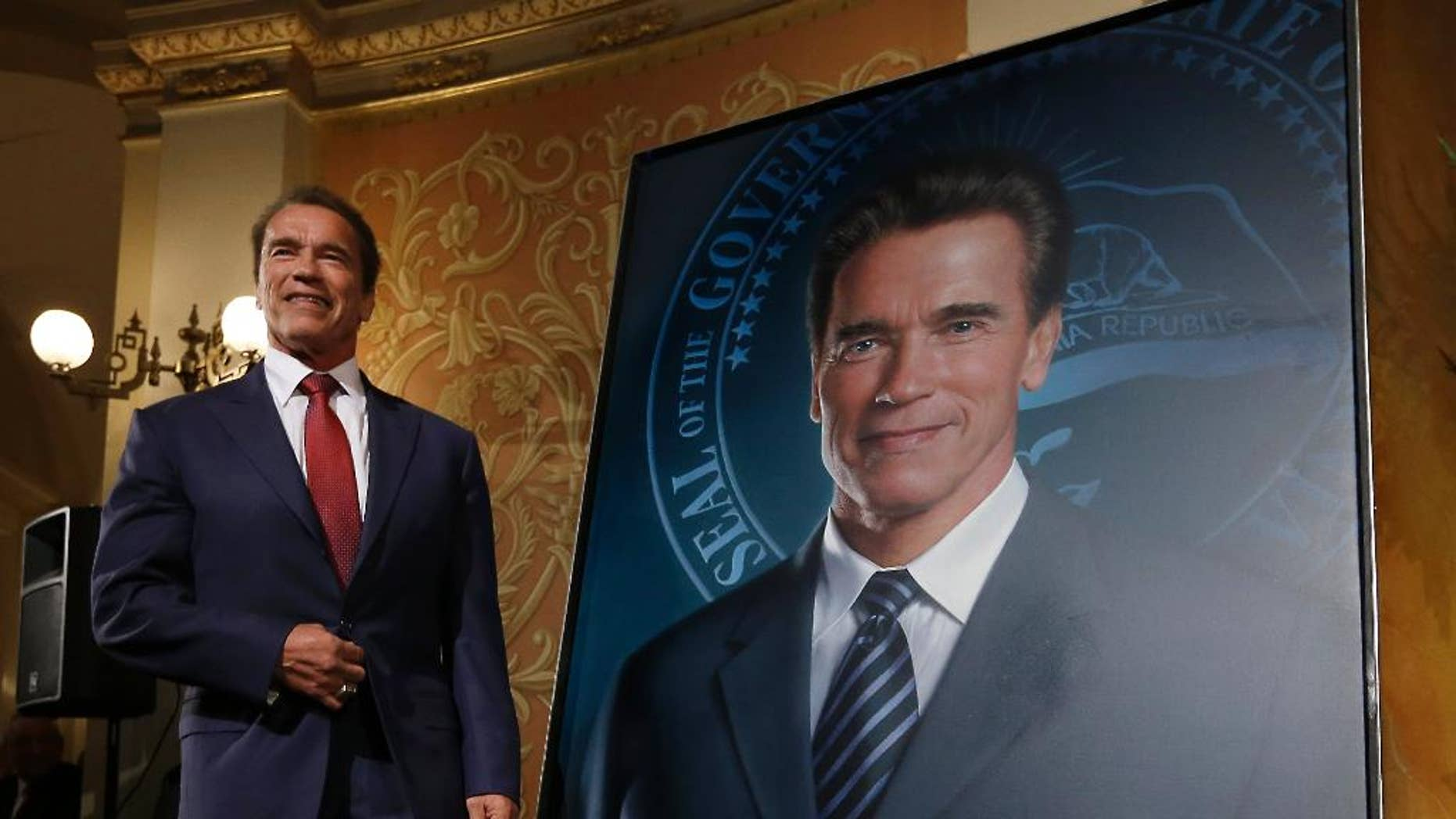 Former Gov. Arnold Schwarzenegger poses with his official portrait after it was unveiled at the Capitol in Sacramento, Calif., Monday, Sept. 8, 2014.  The photograph-like giant image of the former governor was done by Austrian artist Gottfried Helnwein and will hang on the third floor of the Capitol. (AP Photo/Rich Pedroncelli)