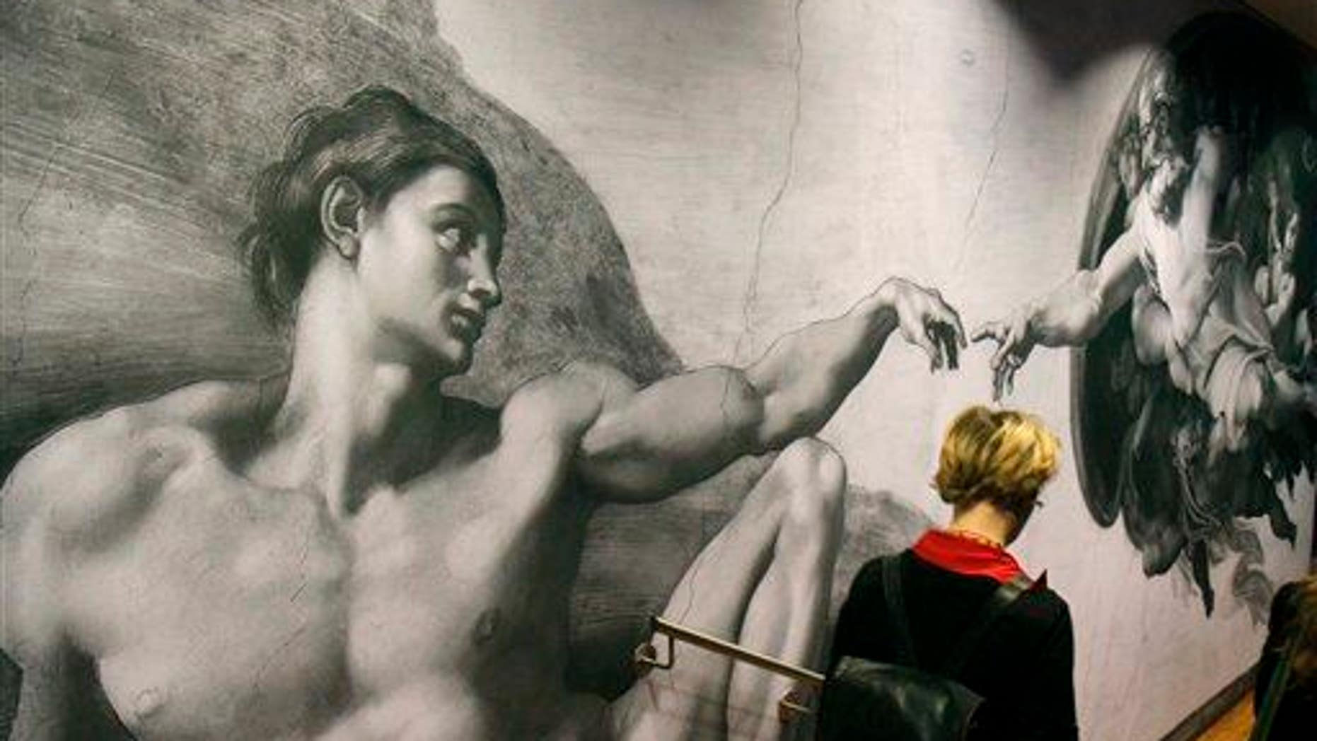 """A visitors passes a poster from the Sistine Chapel showing """"Creation of Adam"""" at the Albertina museum, in Vienna, Austria, on Wednesday, Oct. 6, 2010."""