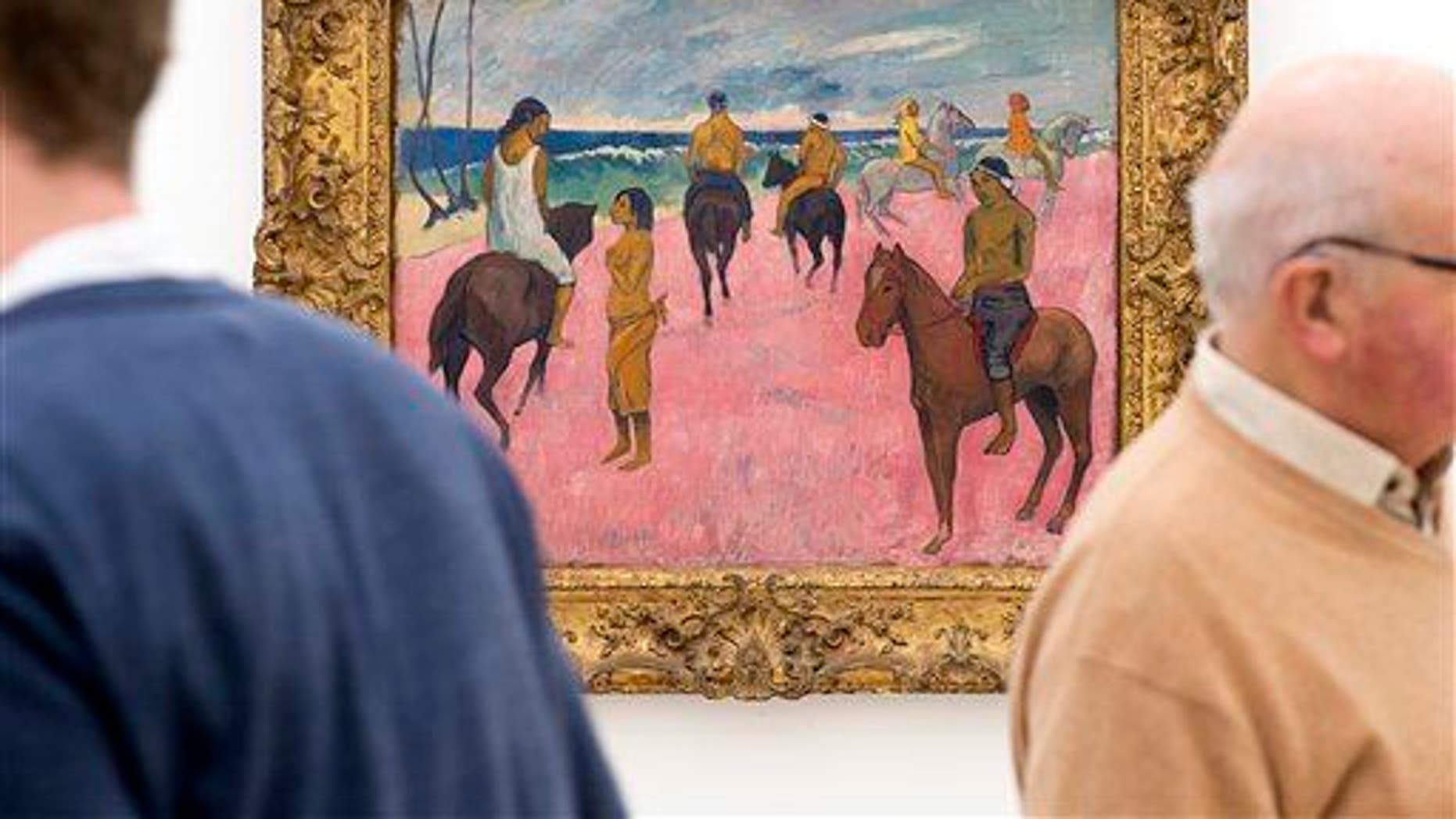 """Two men stand next to """"Cavaliers sur la plage"""" (Riders on the beach, 1902) by French painter Paul Gauguin at an exhibition  in the Fondation Beyeler in Riehen, Switzerland, on Friday, Feb.  6, 2015."""