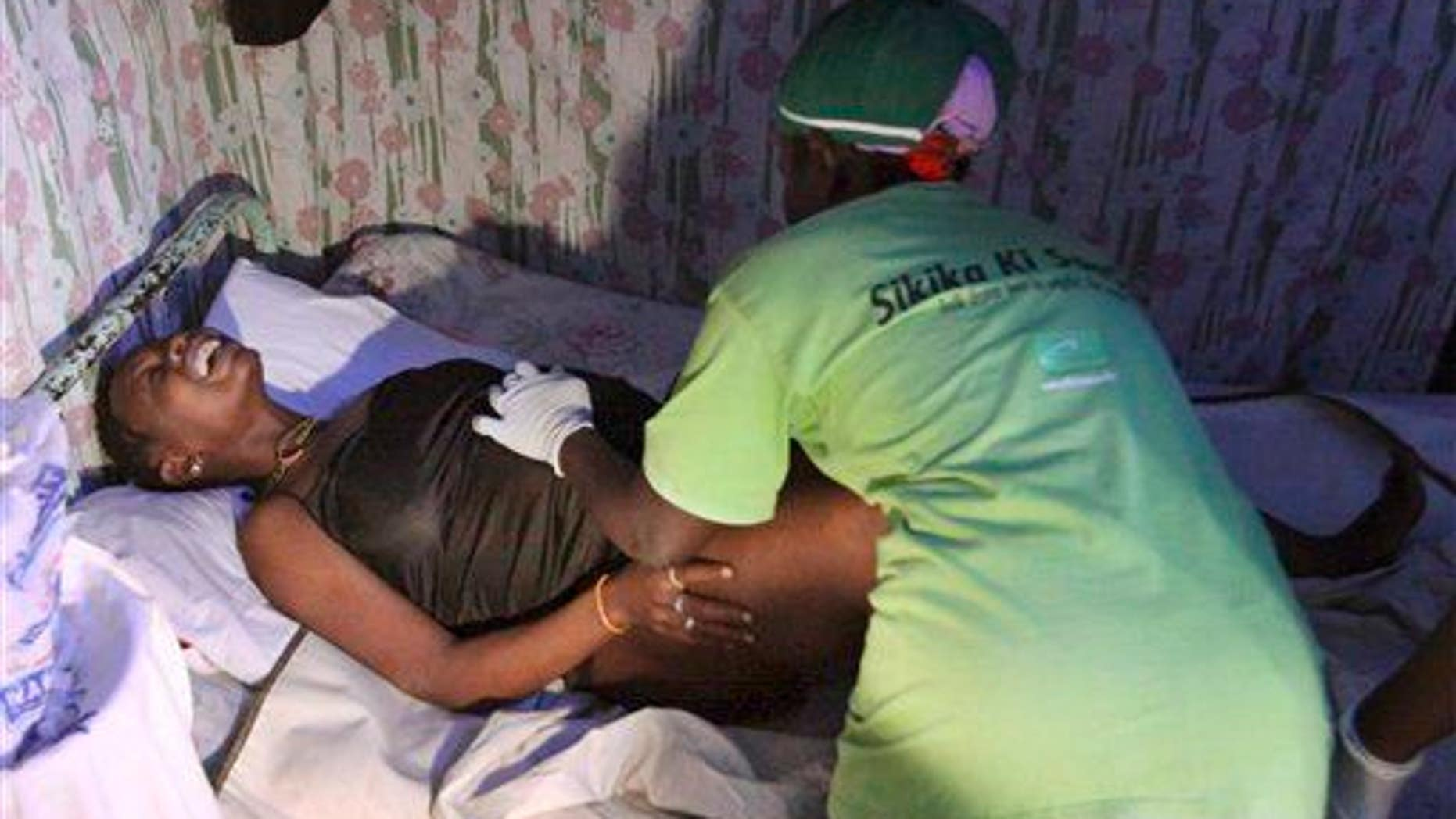 In this July 25, 2010, photo, a traditional birth attendant assists a woman as she goes through labor in Nairobi, Kenya.