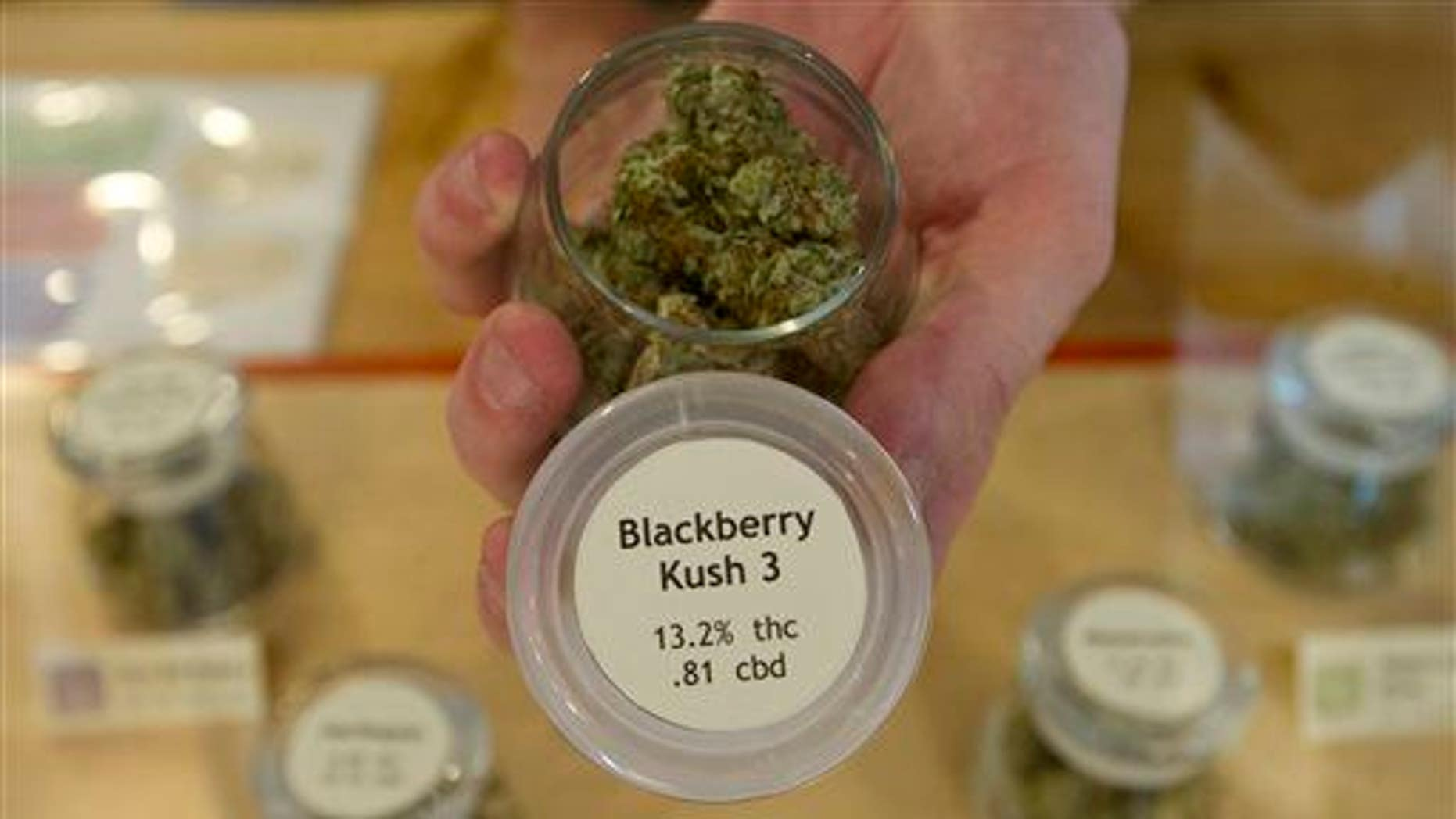 In this photo taken on July 2, 2014, an employee at Bloom Well, a medical marijuana dispensary in Bend, Ore., holds a container of cannabis that is marked with the THC and CBD results.