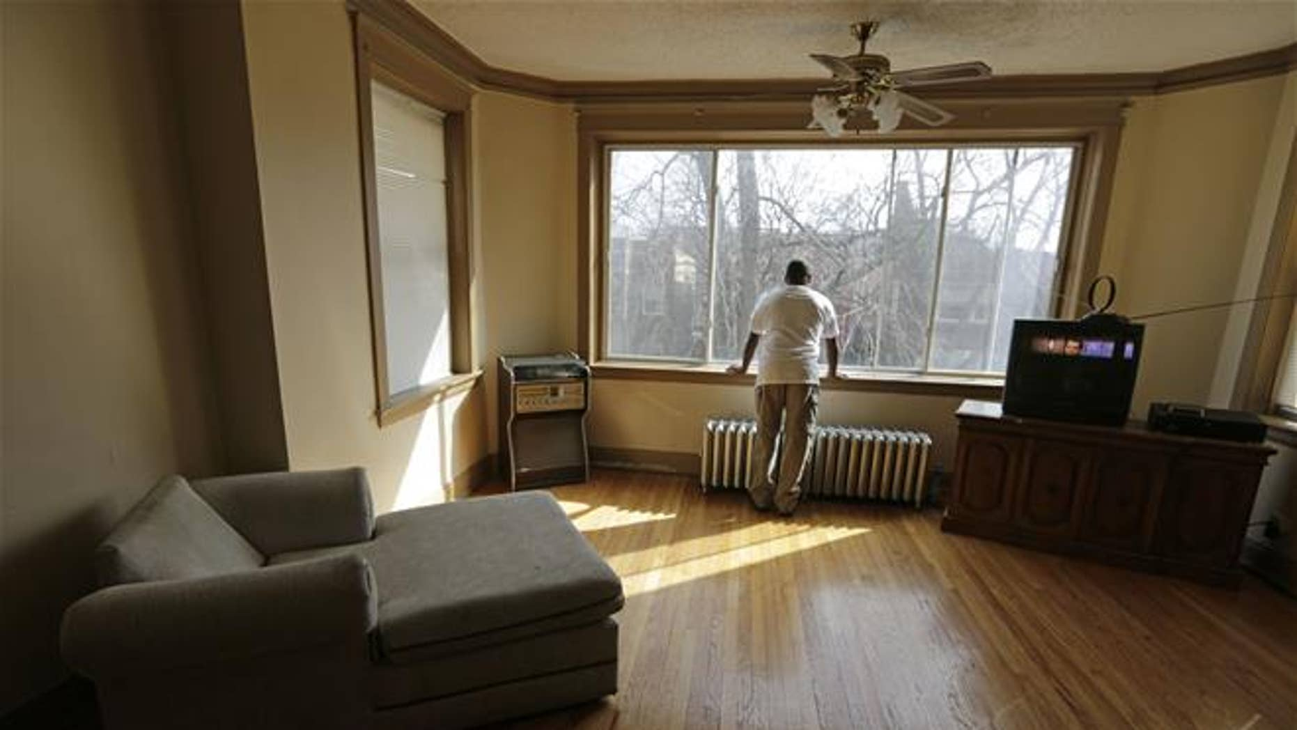 In this March 8, 2016, photo, a resident of a sober home in Chicago looks out the window of his apartment.