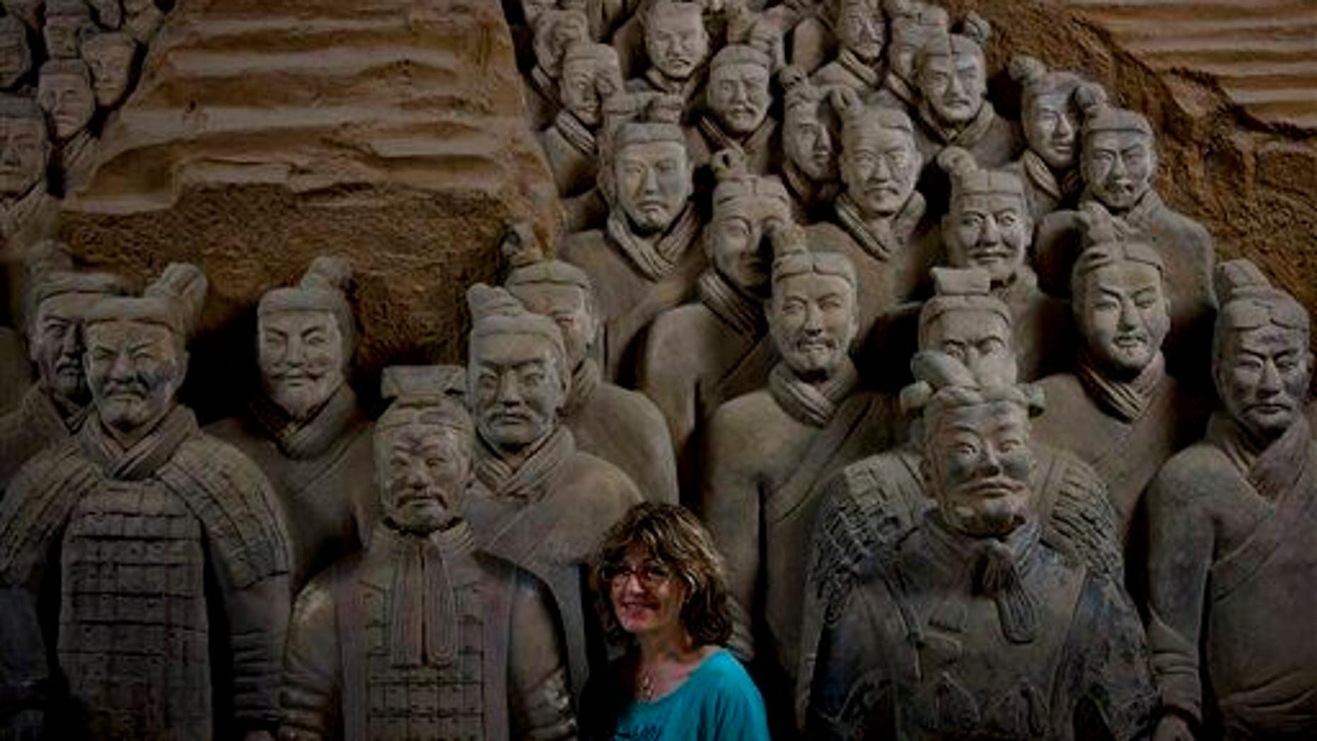 In this July 30, 2013 photo, a tourist stands near a terracotta warrior replica as she poses for a photo at the Museum of Qin Terracotta Warriors and Horses in Xi'an, in China's Shaanxi province.
