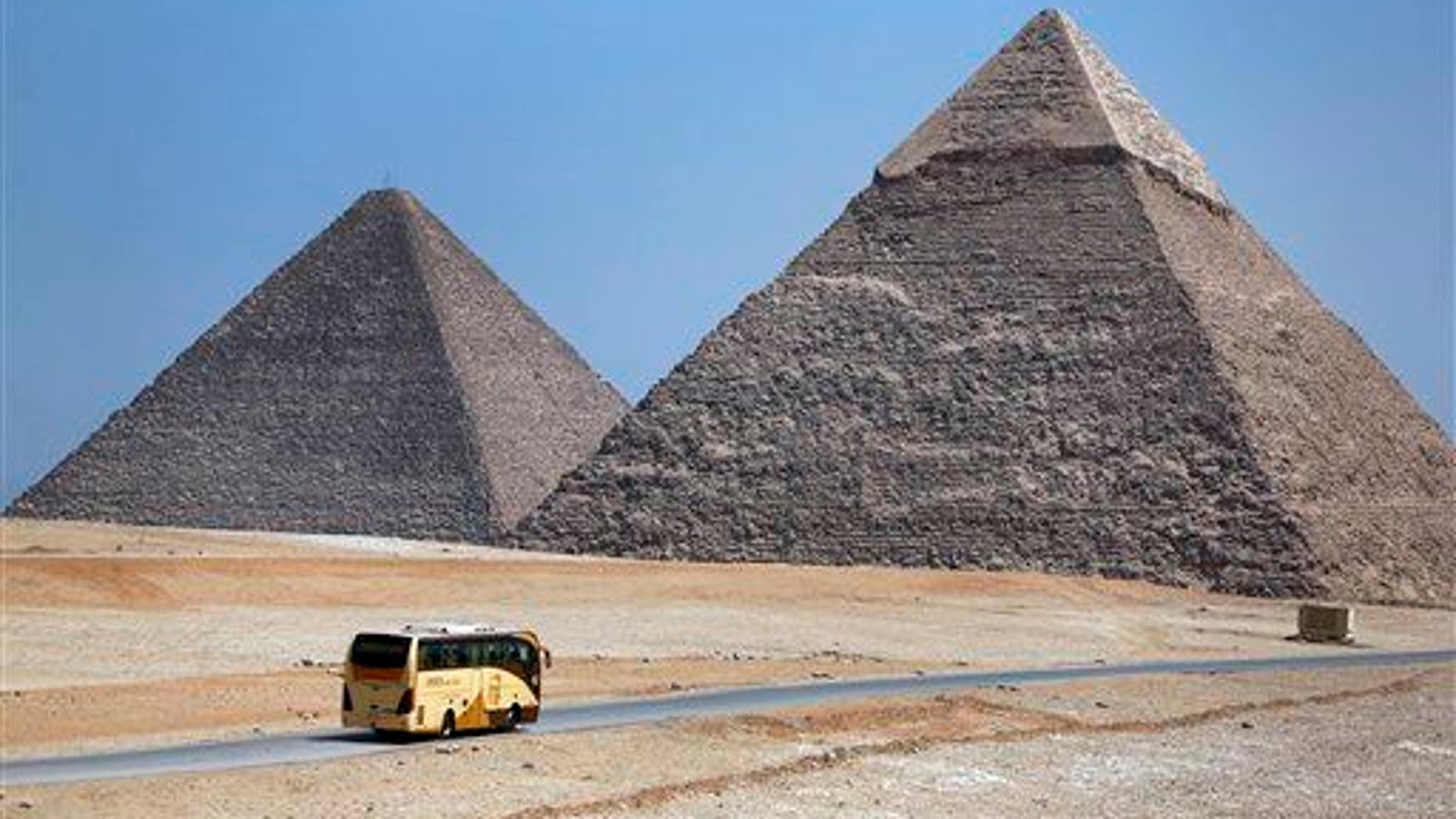 In this Saturday, Sept. 7, 2013 photo, a tour bus passes near the historical site of the Giza Pyramids, near Cairo, Egypt.