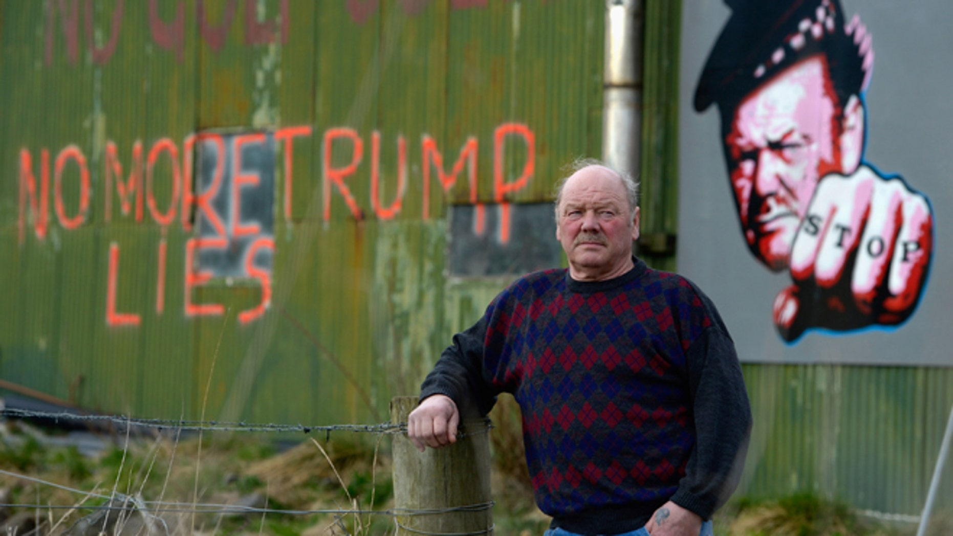 Michael Forbes stands beside his shed, near Donald Trump's golf course.