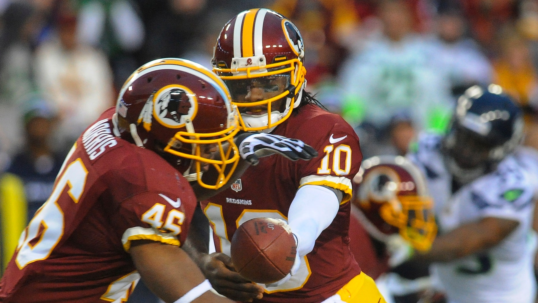 Jan. 6, 2013: Washington Redskins quarterback Robert Griffin III hands off to running back Alfred Morris during the first half of an NFL wild card playoff football game against the Seattle Seahawks in Landover, Md.