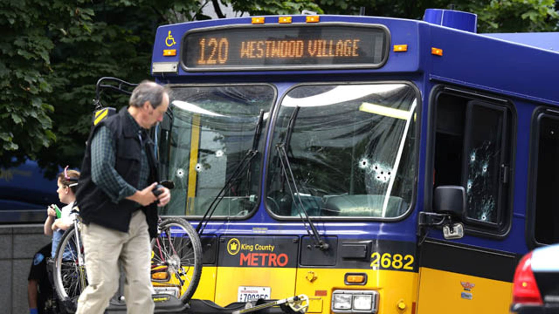 August 12, 2013: An official walks next to a King Co. Metro bus with multiple bullet holes in its windshield and side window, after a bus driver was shot in downtown Seattle. (AP Photo)