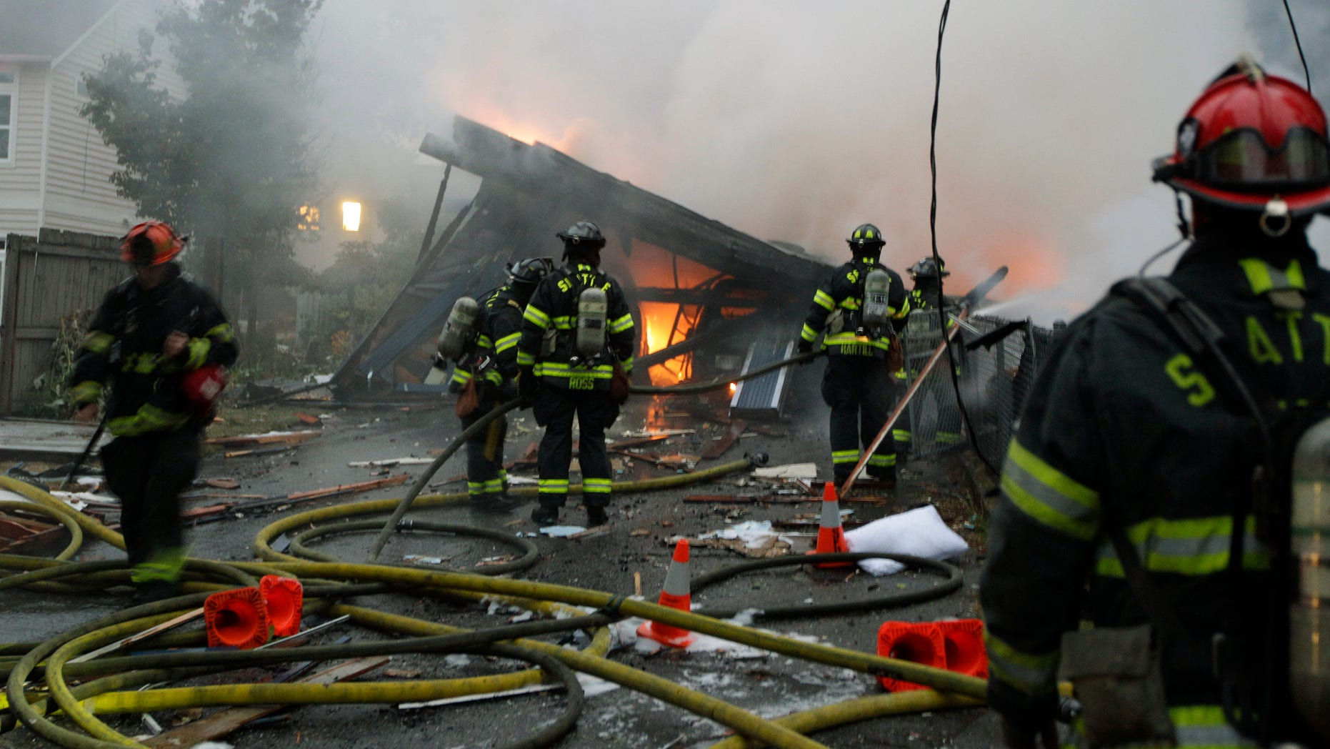 September 26: Seattle firefighters work to extinguish a fire at a home in Seattle following a large explosion. Two people were injured, one with life-threatening injuries and the other is in serious condition.