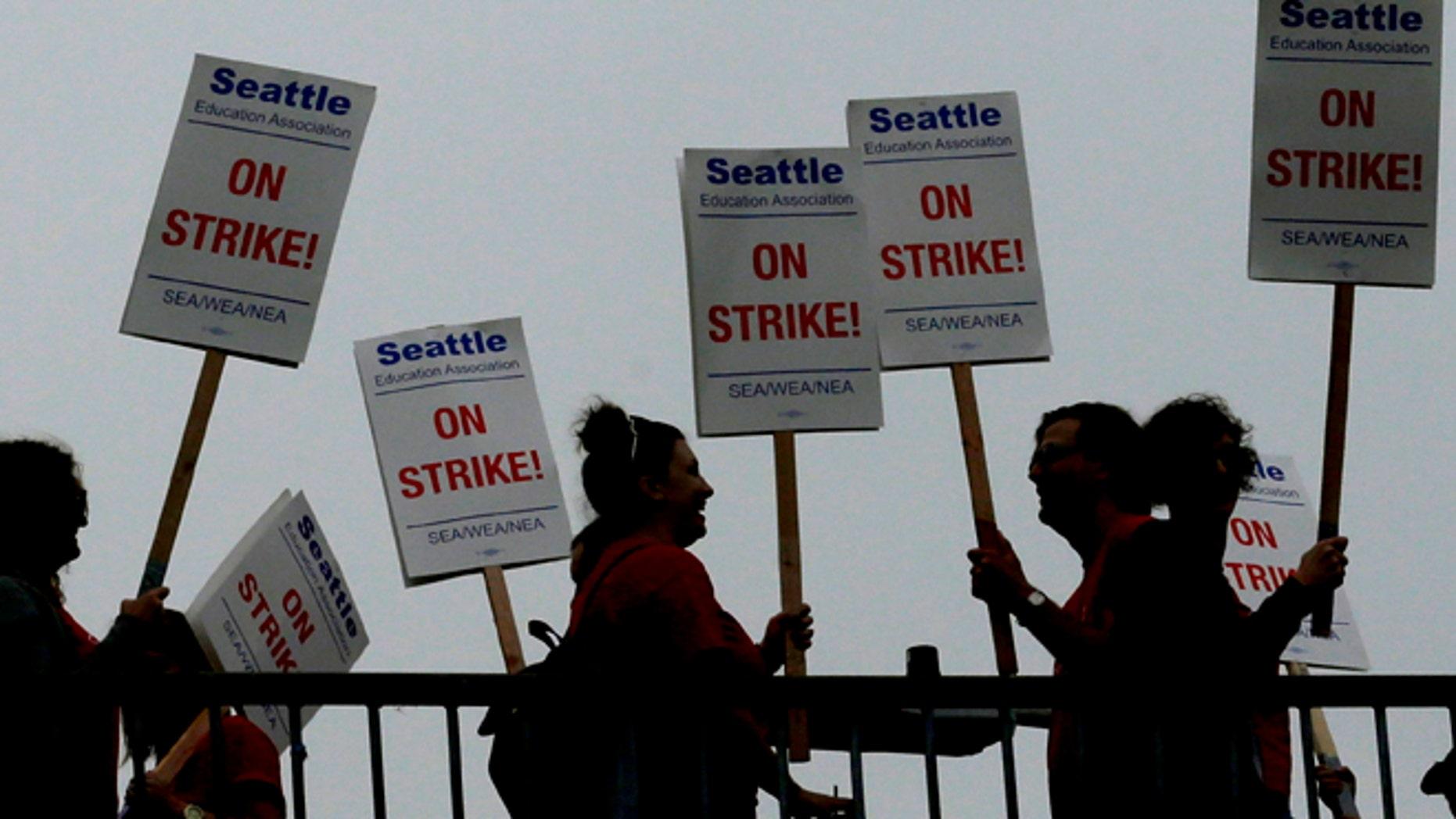 Sept 10: Striking Seattle School District teachers and other educators walk a picket line on a pedestrian overpass.