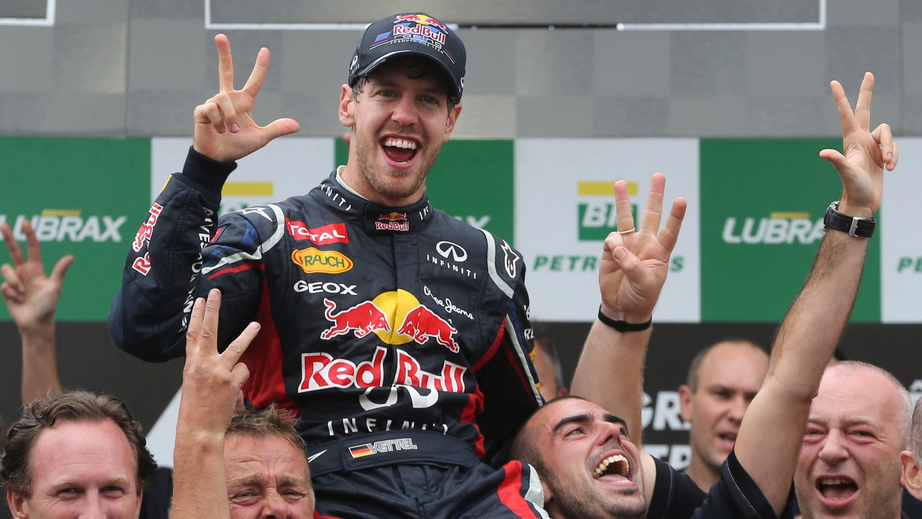 Red Bull driver Sebastian Vettel, center, of Germany, celebrates with members of his team after the Formula One Brazilian Grand Prix at the Interlagos race track in Sao Paulo, Brazil,  Sunday, Nov. 25, 2012. (AP Photo/Andre Penner)