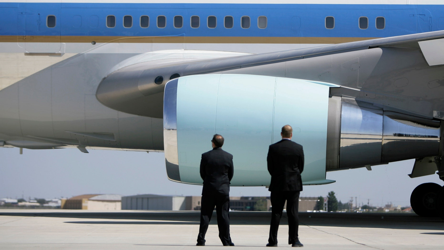 In this Saturday, Oct. 4, 2008 photo, Secret Service agents watch as Air Force One departs Midland International Airport with President Bush and first lady Laura Bush aboard in Midland, Texas. (AP Photo/Matt Slocum)
