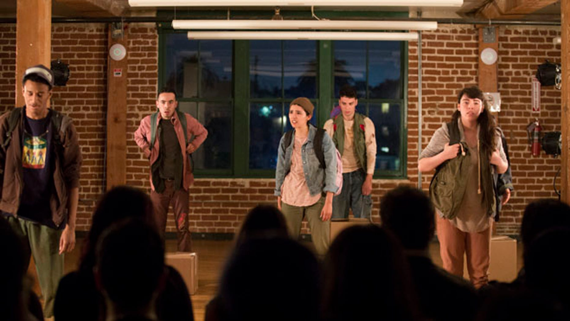 """In this Friday, March 18, 2016 photo, from left, actors Julien Moore, Julian Sandoval, Cynthia Callejas, Peter Mark and Audrey Olmos perform in the play """"Shelter"""" at CalArts Center for New Performance in Los Angeles. For Sandoval, the play """"Shelter"""" is more than just a story of children flooding into the U.S. by the tens of thousands from Latin America in search of safe sanctuary. It's personal. The young actor's mother immigrated to the U.S. illegally years ago, fleeing the violence of her native El Salvador after seeing a cousin hacked to death by soldiers with machetes during the country's civil war. She would become a legal resident under the Immigration Reform and Control Act of 1986 and eventually a U.S. citizen. (AP Photo/ Jenna Schoenefeld)"""
