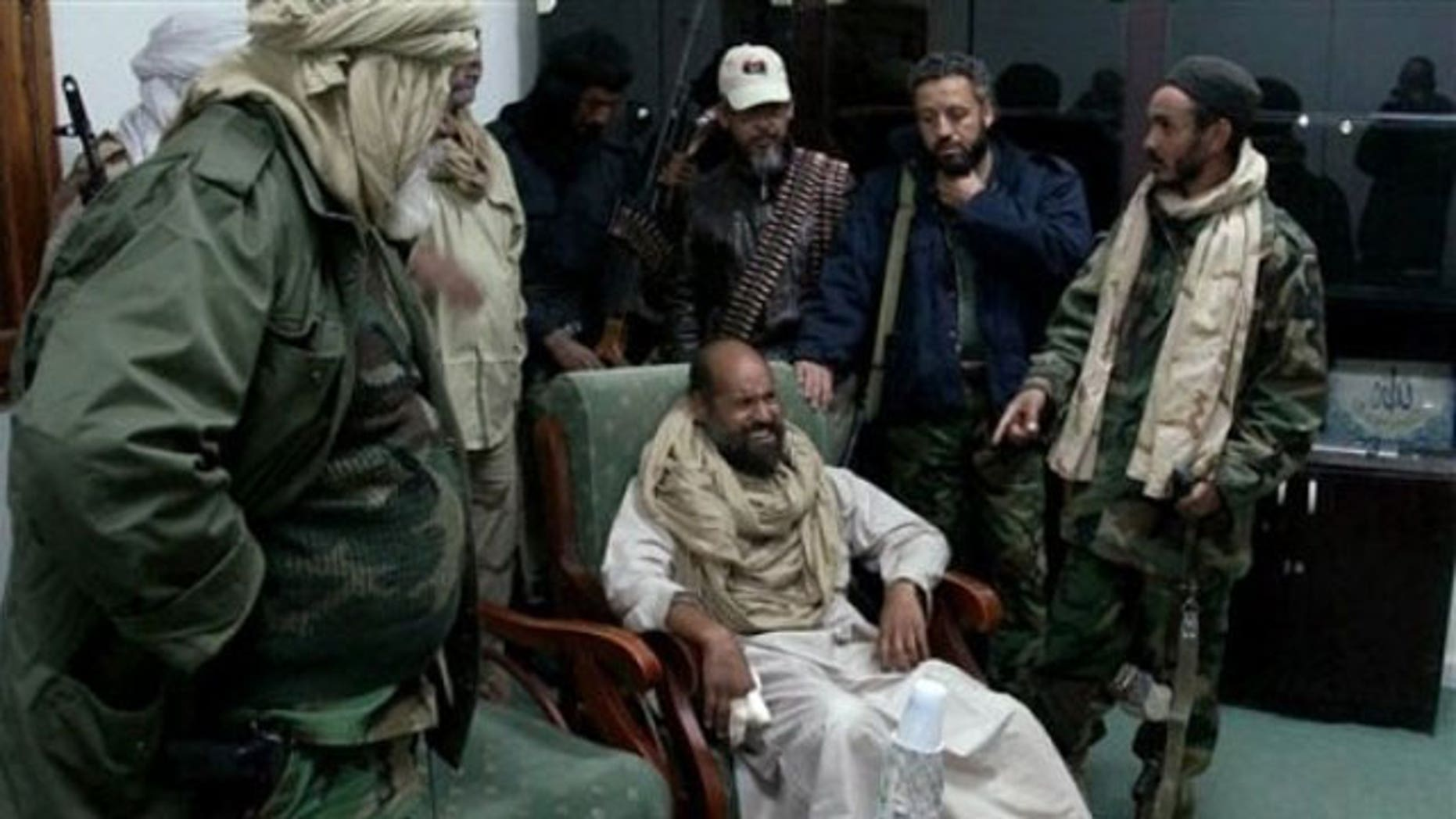 November 22, 2011: In this image taken from new video which has become available showing of Muammar Qaddafi's son Seif al-Islam, sitting at centre, wincing in pain from his injured fingers, in video taken shortly after his capture on Nov. 19, 2011, at a safe house in the town of Zintan, Libya.