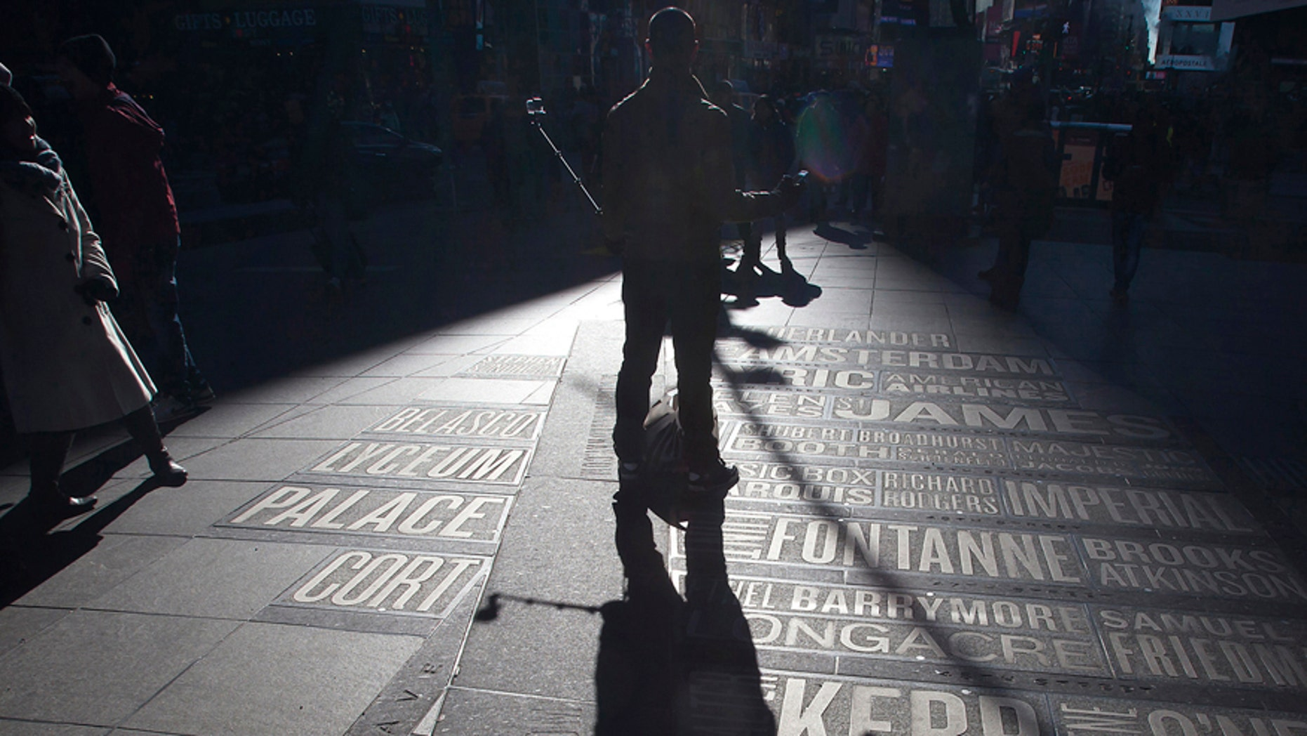 A man uses a selfie stick to take his own photos in Times Square in the Manhattan borough of New York Jan.17, 2015.